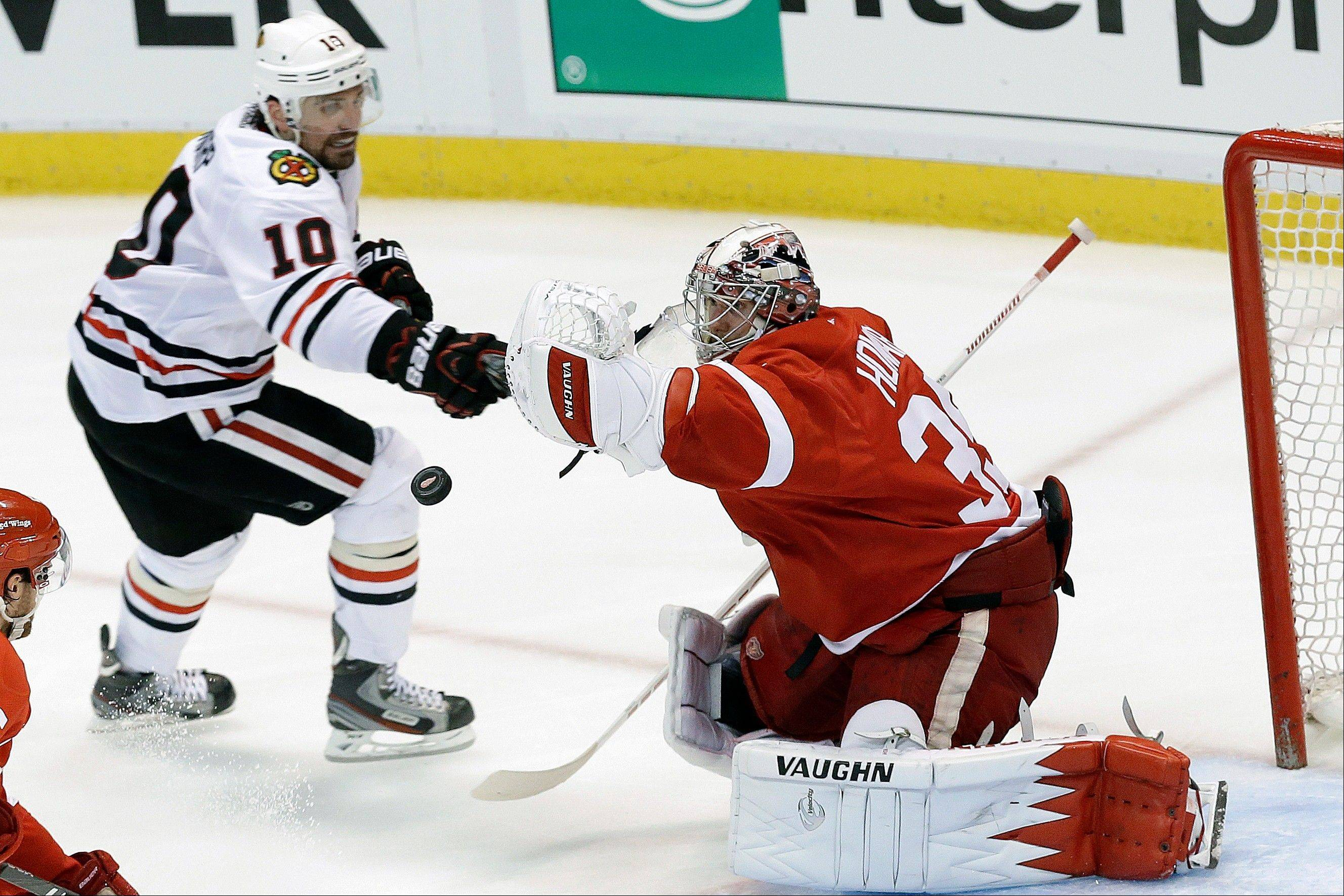 Red Wings goalie Jimmy Howard stops a shot by the Blackhawks' Patrick Sharp during the third period Monday night.