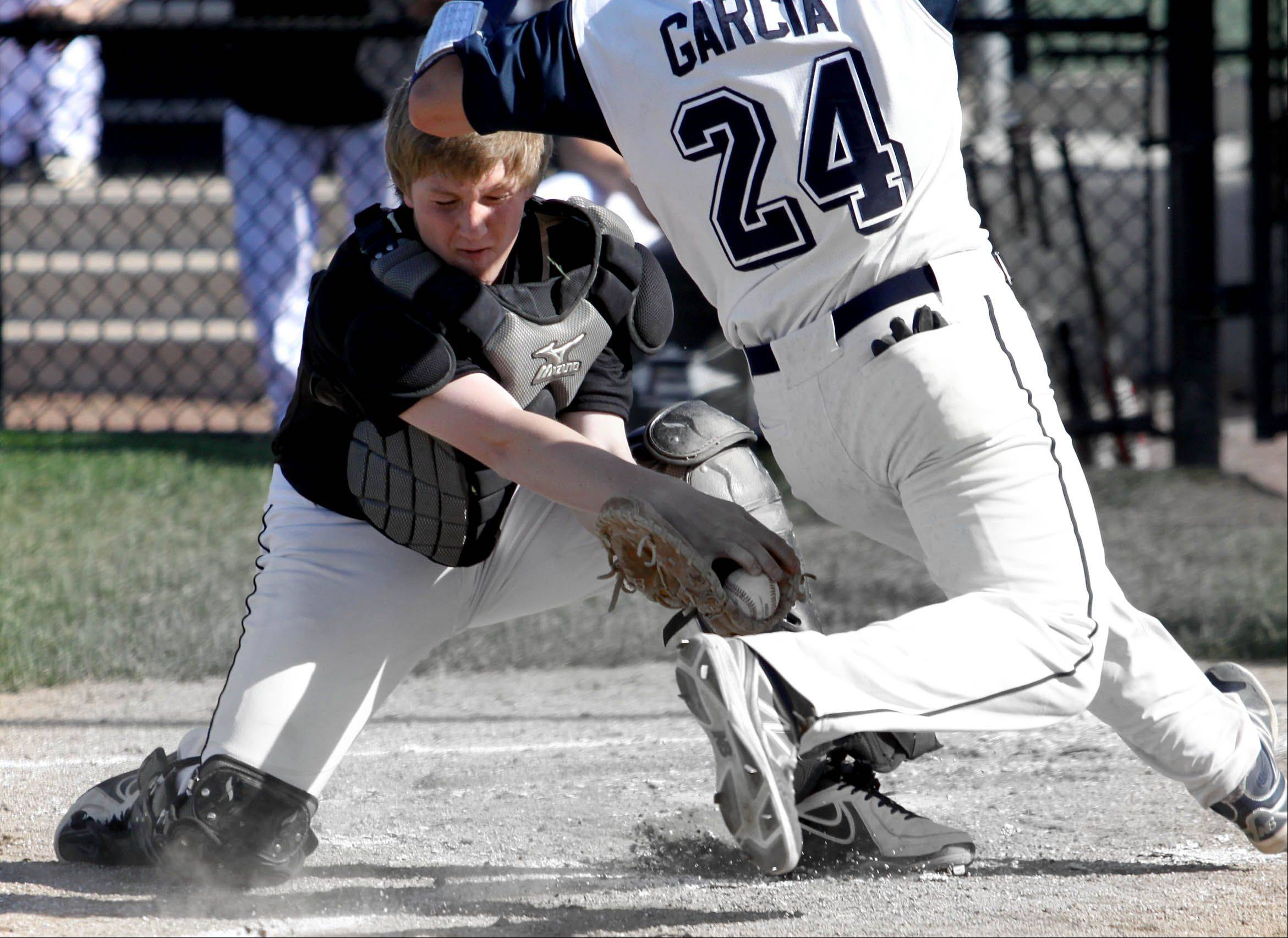 Bev Horne/bhorne@dailyherald.comCatcher Troy Caminitti of Streamwood tags out Jordan Garcia of Addison Trail at home plate in baseball action on Monday in Addison.