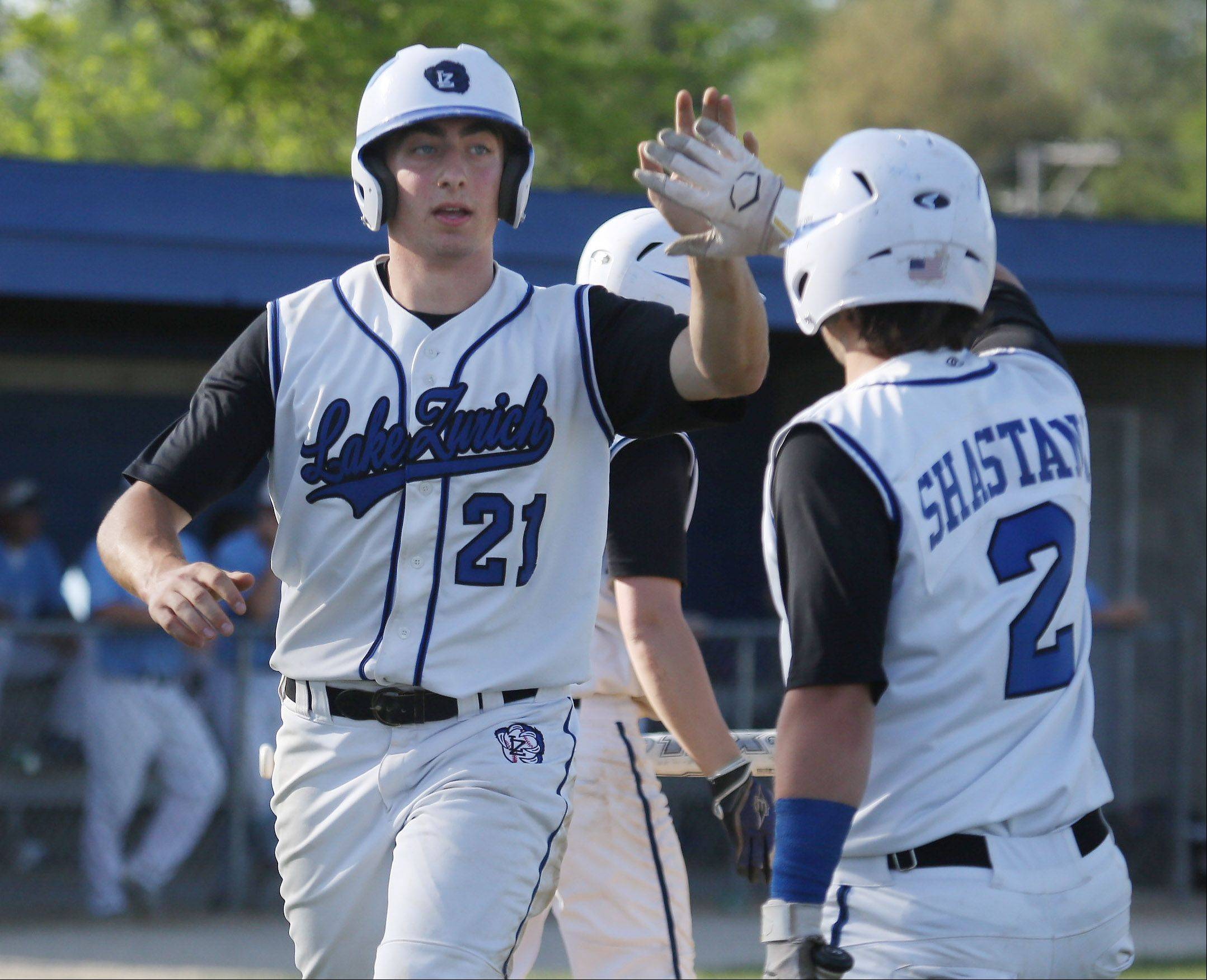 Lake Zurich hitter Dominic DeMicco is congratulated by teammate Mike Shastany after scoring in the second inning against Prospect in Class 4A regional play Monday.