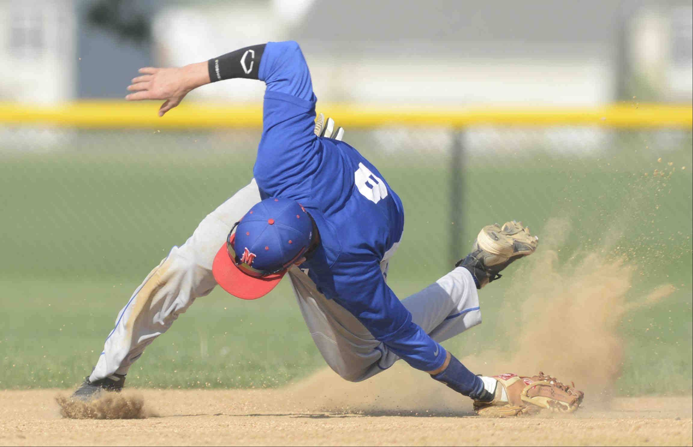 Marmion Academy shortstop Josh Meyers falls as he stops a sharp ground ball by West Aurora's Adam Lipscomb in the second inning Monday in Aurora. he was unable to make a play, but stopped a run from scoring.