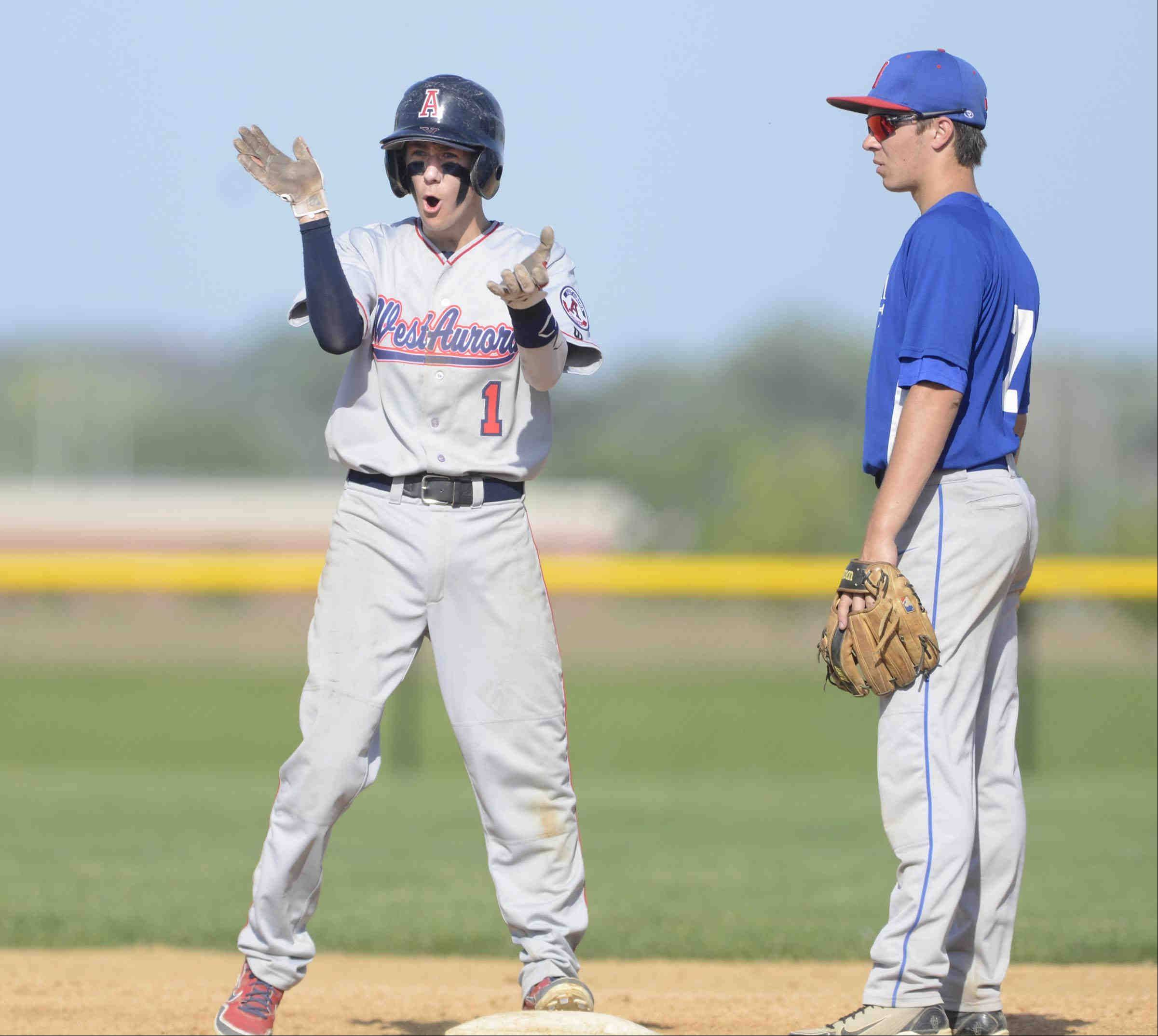 West Aurora's Michael Golich encourages his teammates after hitting a double in the second inning against Marmion Academy Monday in Aurora, as Marmion second baseman Will Dorjath looks on.