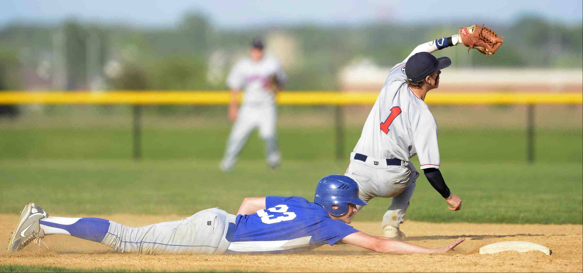 Marmion Academy's Alex Troop reaches back safely for second base as the pick off throw from the catcher goes over West Aurora shortstop Michael Golich Monday in Aurora.