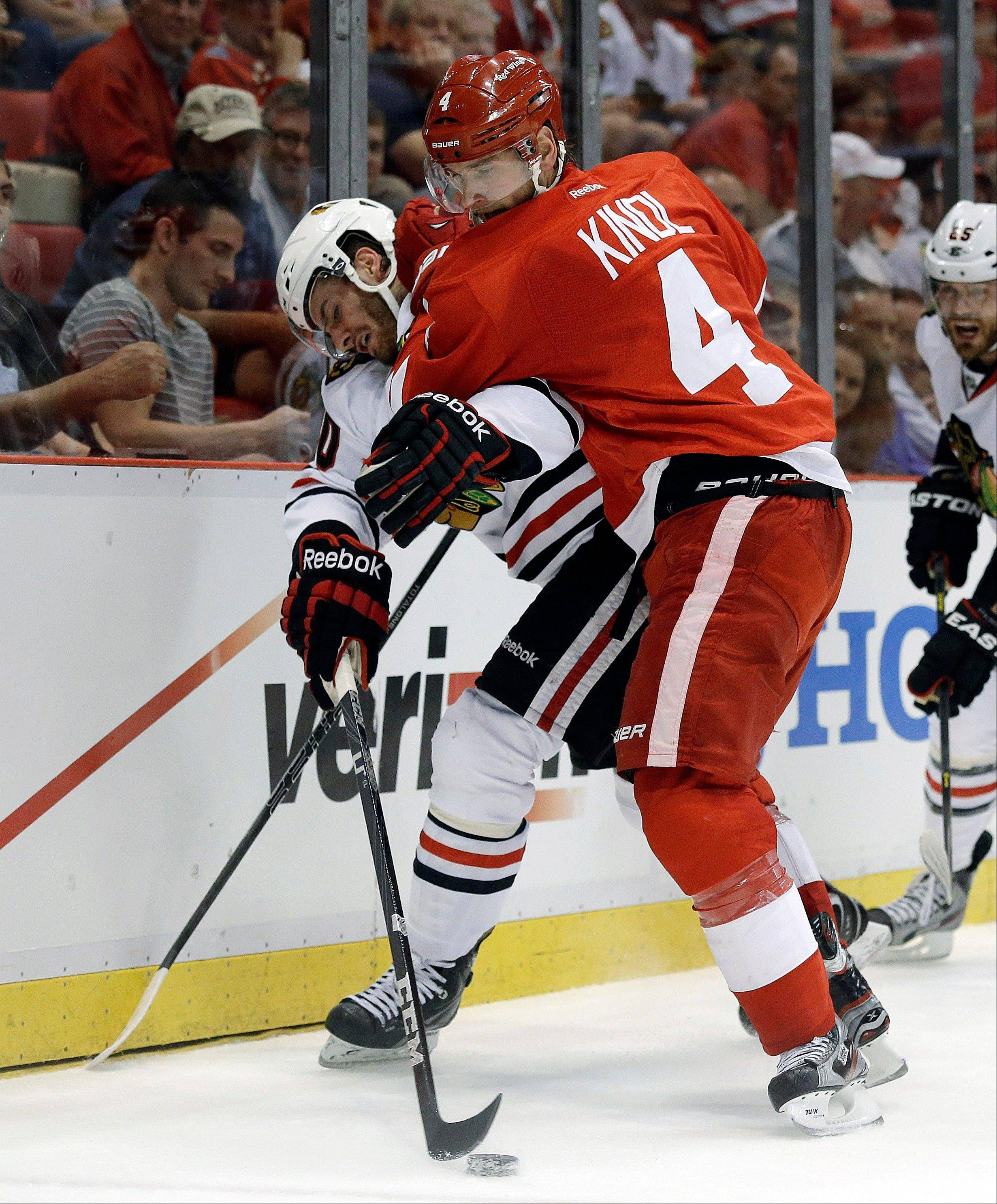 Detroit Red Wings defenseman Jakub Kindl (4), of the Czech Republic, checks Chicago Blackhawks left wing Brandon Saad (20) during the first period of an NHL hockey Stanley Cup playoffs Western Conference semifinal game in Detroit, Monday, May 20, 2013.