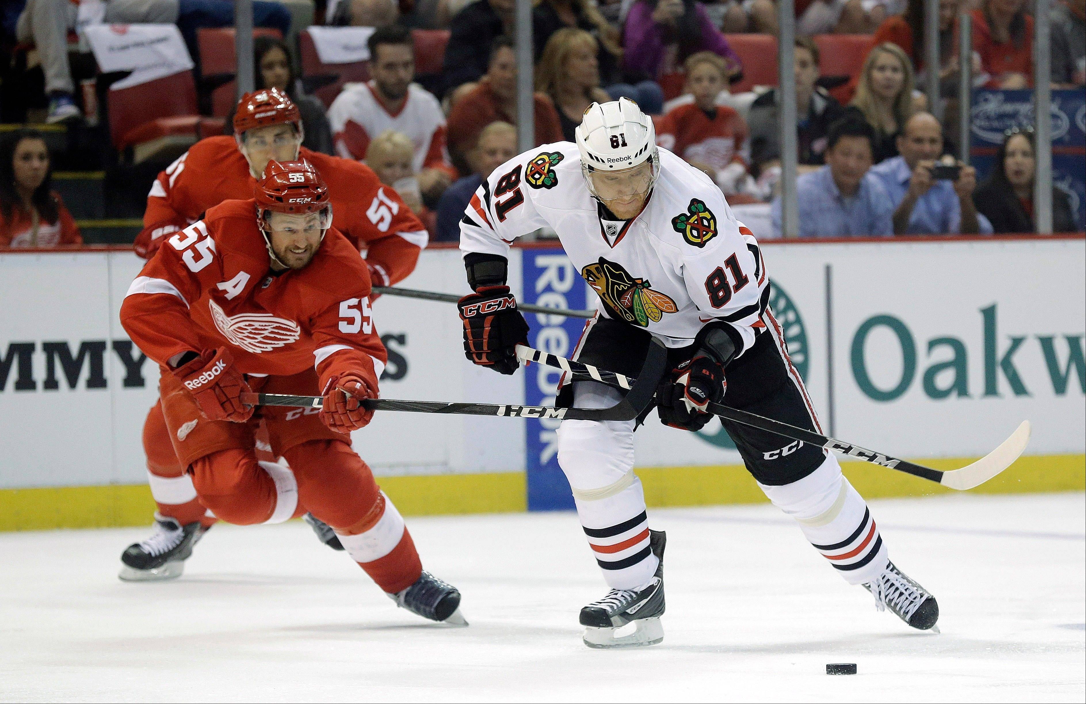 Detroit Red Wings defenseman Niklas Kronwall (55), of Sweden, tries to slow Chicago Blackhawks right wing Marian Hossa (81), of the Czech Republic, during the first period of an NHL hockey Stanley Cup playoffs Western Conference semifinal game in Detroit, Monday, May 20, 2013.