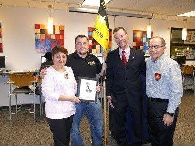 Scott Stratton and Justin Miller welcome Roy and Georgette Frank to the DeVry Military Resource Center Open House. Georgette holds a book with the names of Illinois military who gave their lives in Iraq or Afghanistan.