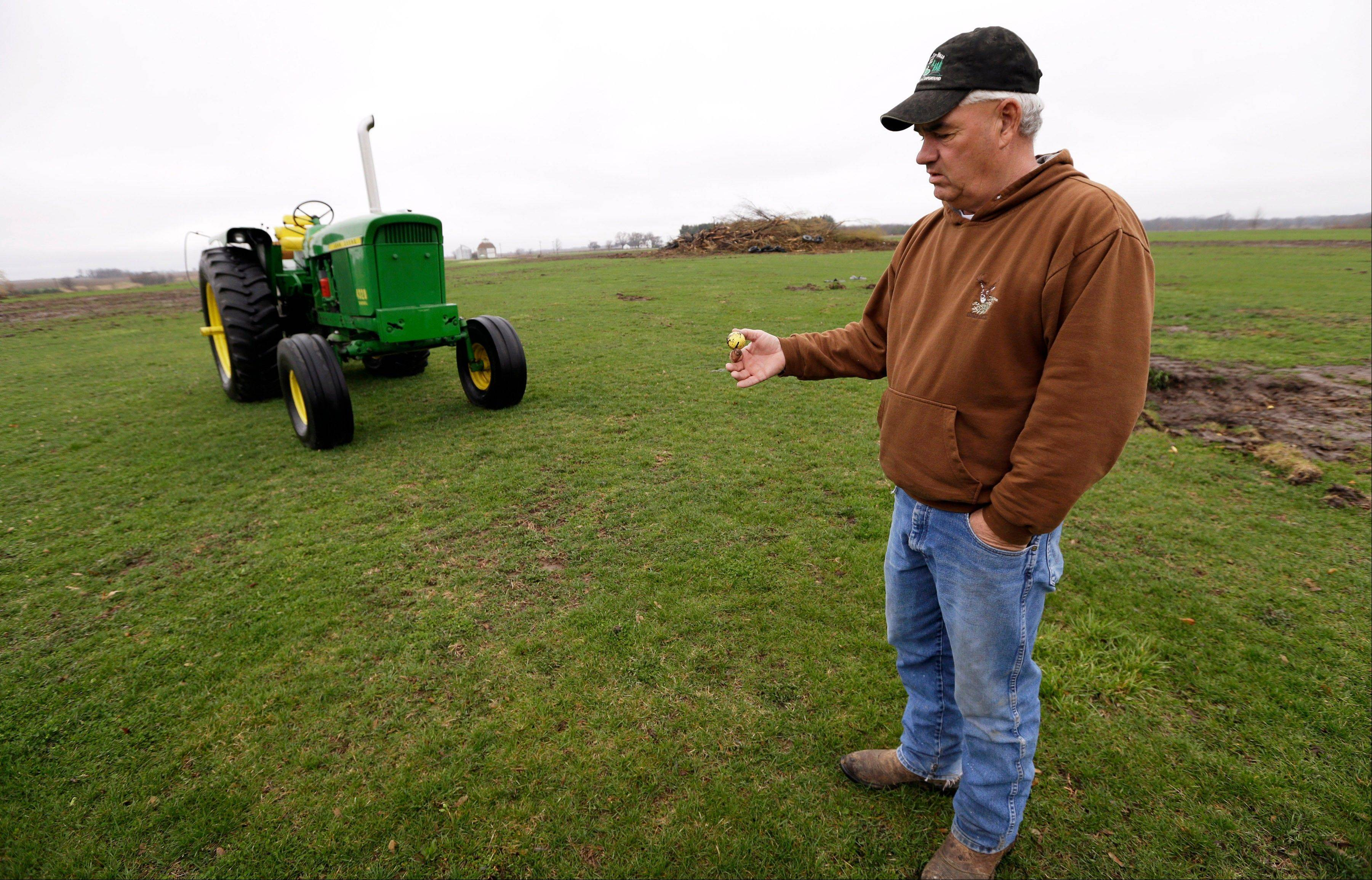 Farmer Clark Kelly holds a golf ball he dug out of a fairway on the Hend-Co-Hills Golf Course, in Biggsville, Ill.