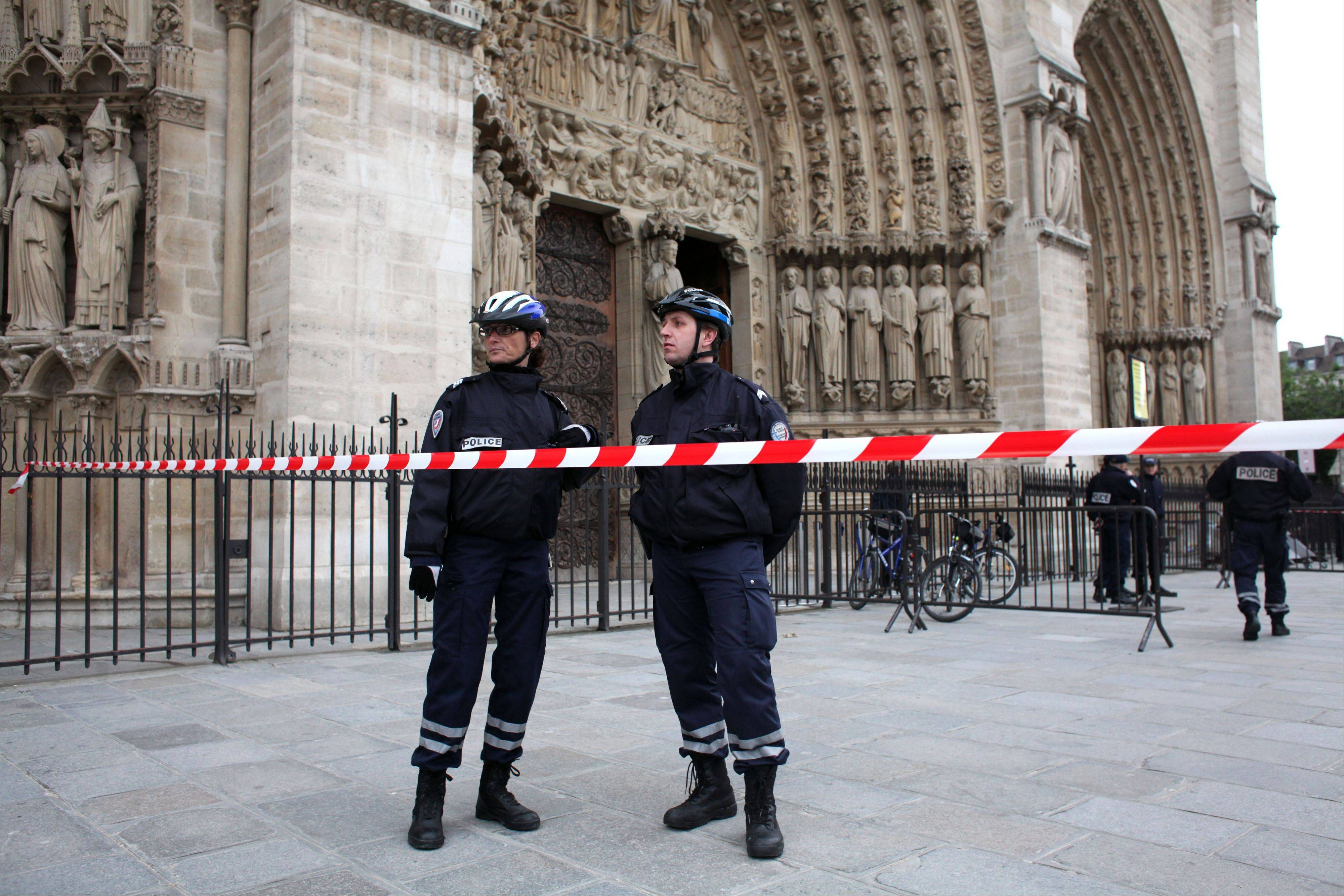 Police officers stand guard in front of Notre Dame Cathedral, in Paris, Tuesday, May 21, 2013. Notre Dame was evacuated after a man committed suicide in the 850-year-old monument and tourist attraction.