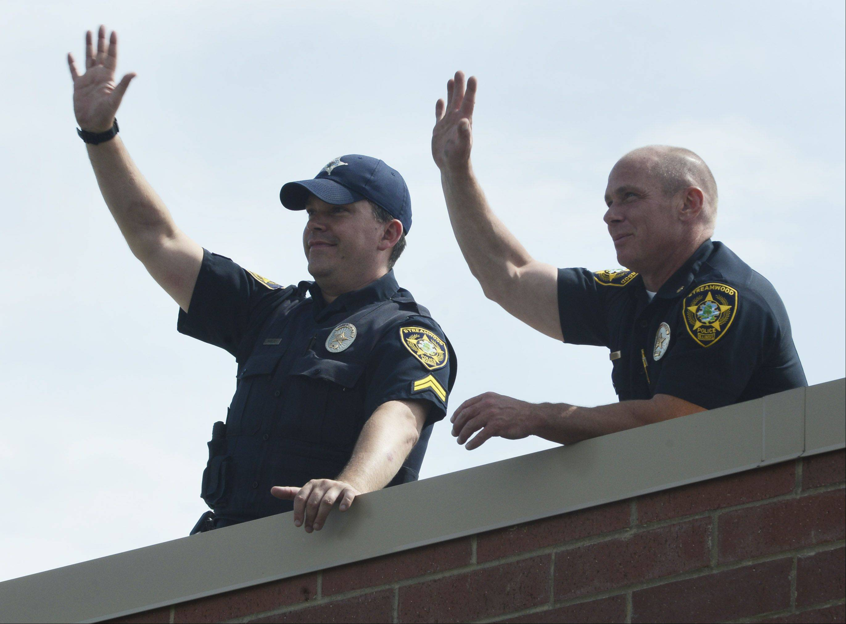 "JOE LEWNARD/jlewnard@dailyherald.comStreamwood Police Department Cpl. Peter Woolsey, left, and Cmdr. John Sunter wave to patrons from the roof of the Dunkin' Donuts, 656 S. Sutton Road, Streamwood, during the annual ""Cop on a Rooftop"" fundraiser for Special Olympics Illinois."