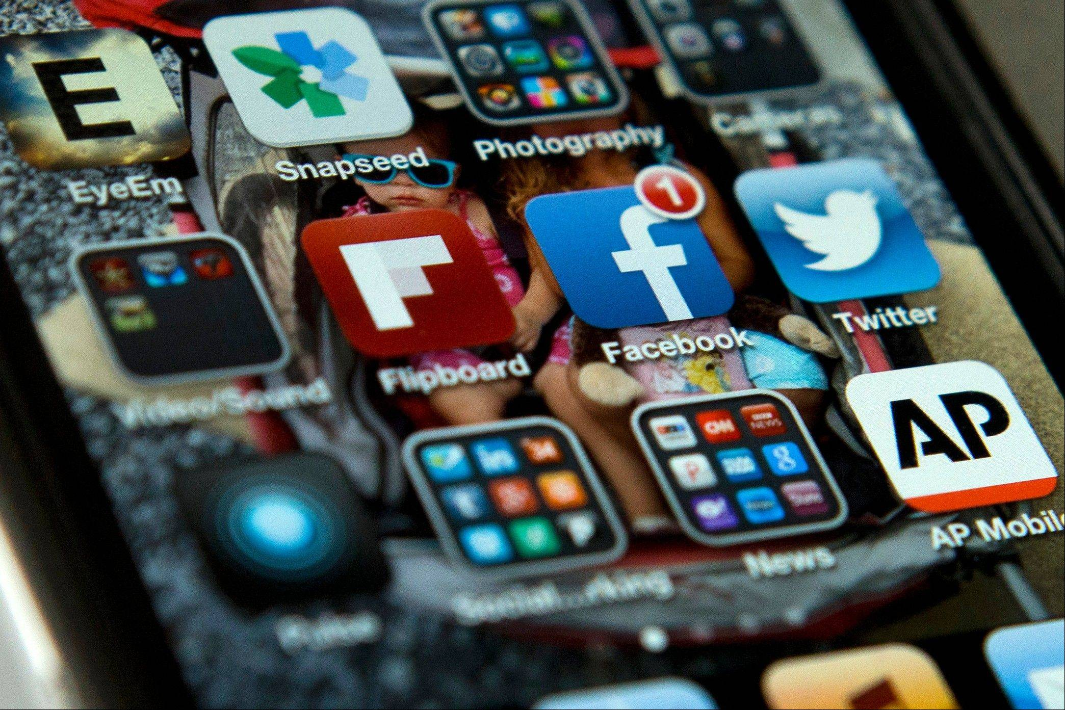 "A view of an iPhone, showing the Twitter and Facebook apps among others. A new poll finds that teens are sharing more about themselves on social media. They're also moving increasingly to Twitter to avoid their parents and the ""oversharing"" that they see on Facebook."