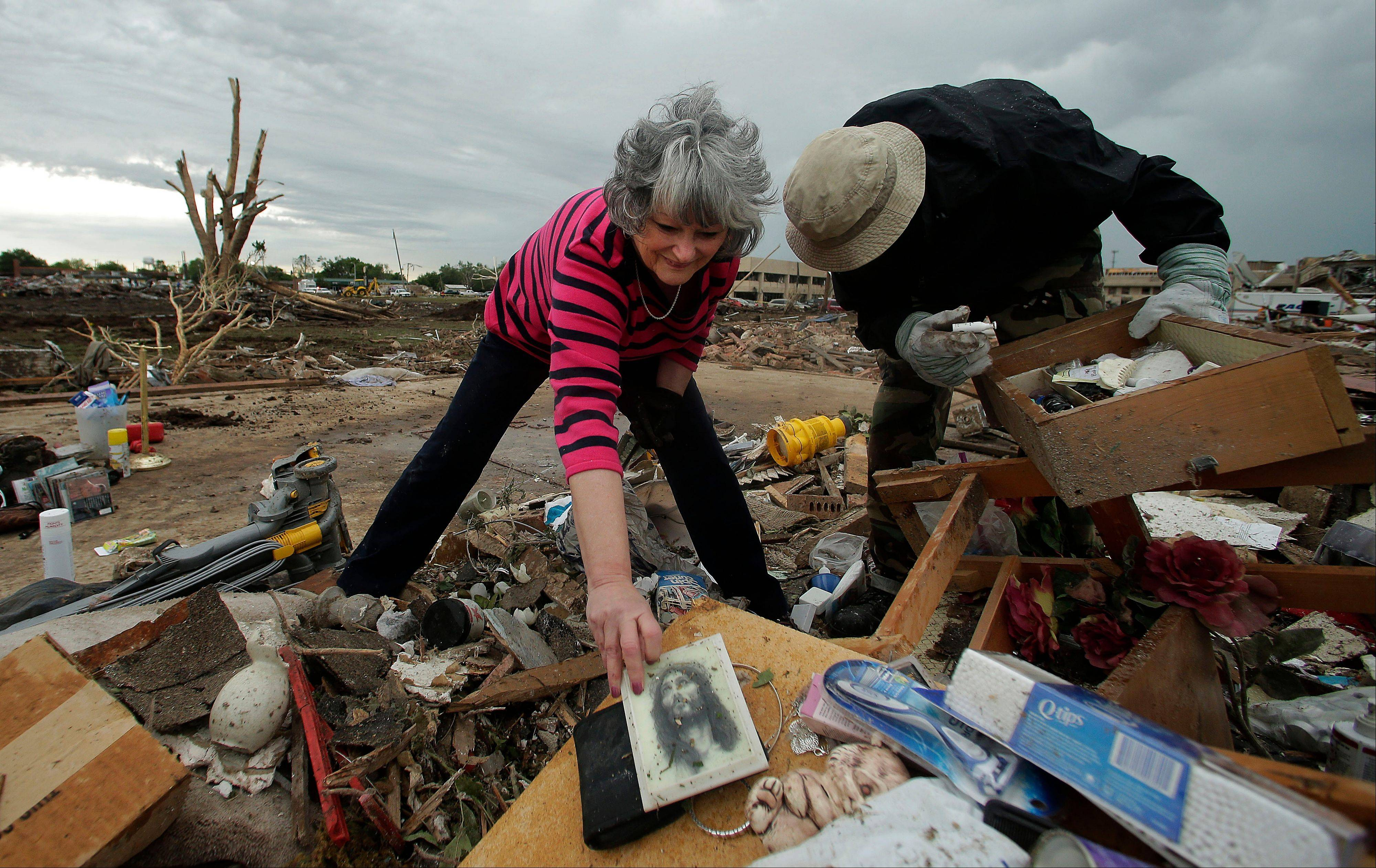 Lea Bessinger salvages a picture of Jesus as she and her son Josh Bessinger sort through the rubble of the elder Bessinger's tornado-ravaged home Tuesday, May 21, 2013, in Moore, Okla. A huge tornado roared through the Oklahoma City suburb Monday, flattening an entire neighborhoods and destroying an elementary school with a direct blow as children and teachers huddled against winds.