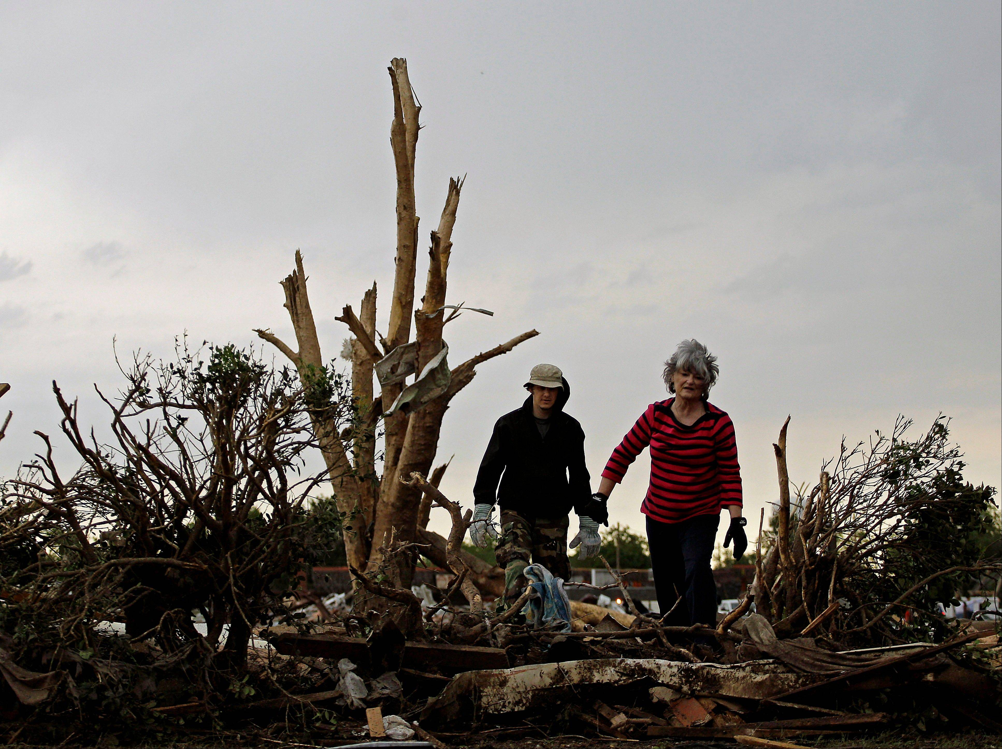 Lea Bessinger and her son Josh Bessinger look through the rubble of the elder Bessinger's tornado-ravaged home Tuesday, May 21, 2013, in Moore, Okla. A huge tornado roared through the Oklahoma City suburb Monday, flattening an entire neighborhoods and destroying an elementary school with a direct blow as children and teachers huddled against winds.
