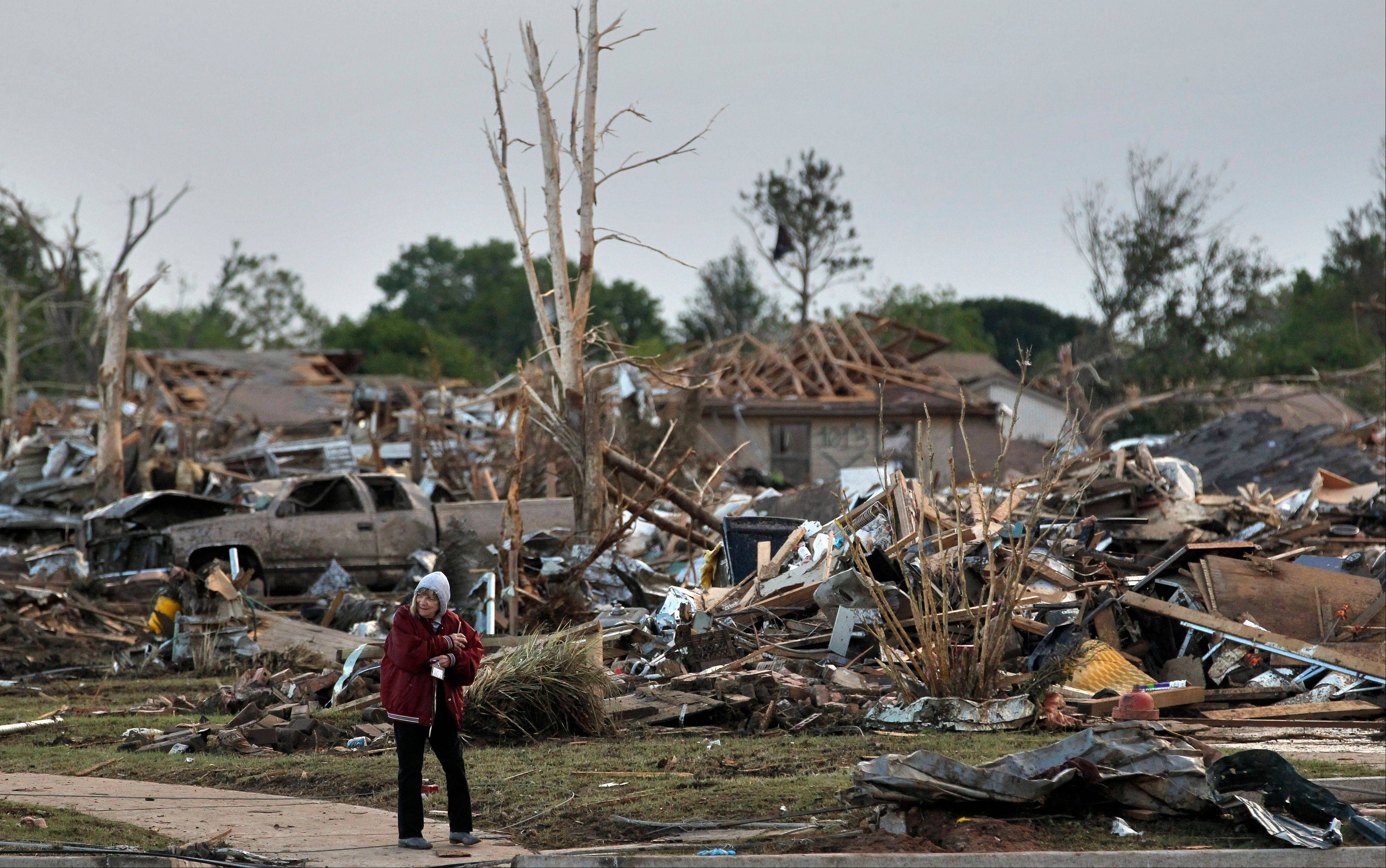 A local resident allowed by security officers into an otherwise sealed off neighborhood walks past the rubble of destroyed homes, one day after a tornado moved through Moore, Okla., Tuesday, May 21, 2013. The huge tornado roared through the Oklahoma City suburb Monday, flattening entire neighborhoods and destroying an elementary school with a direct blow as children and teachers huddled against winds up to 200 mph.