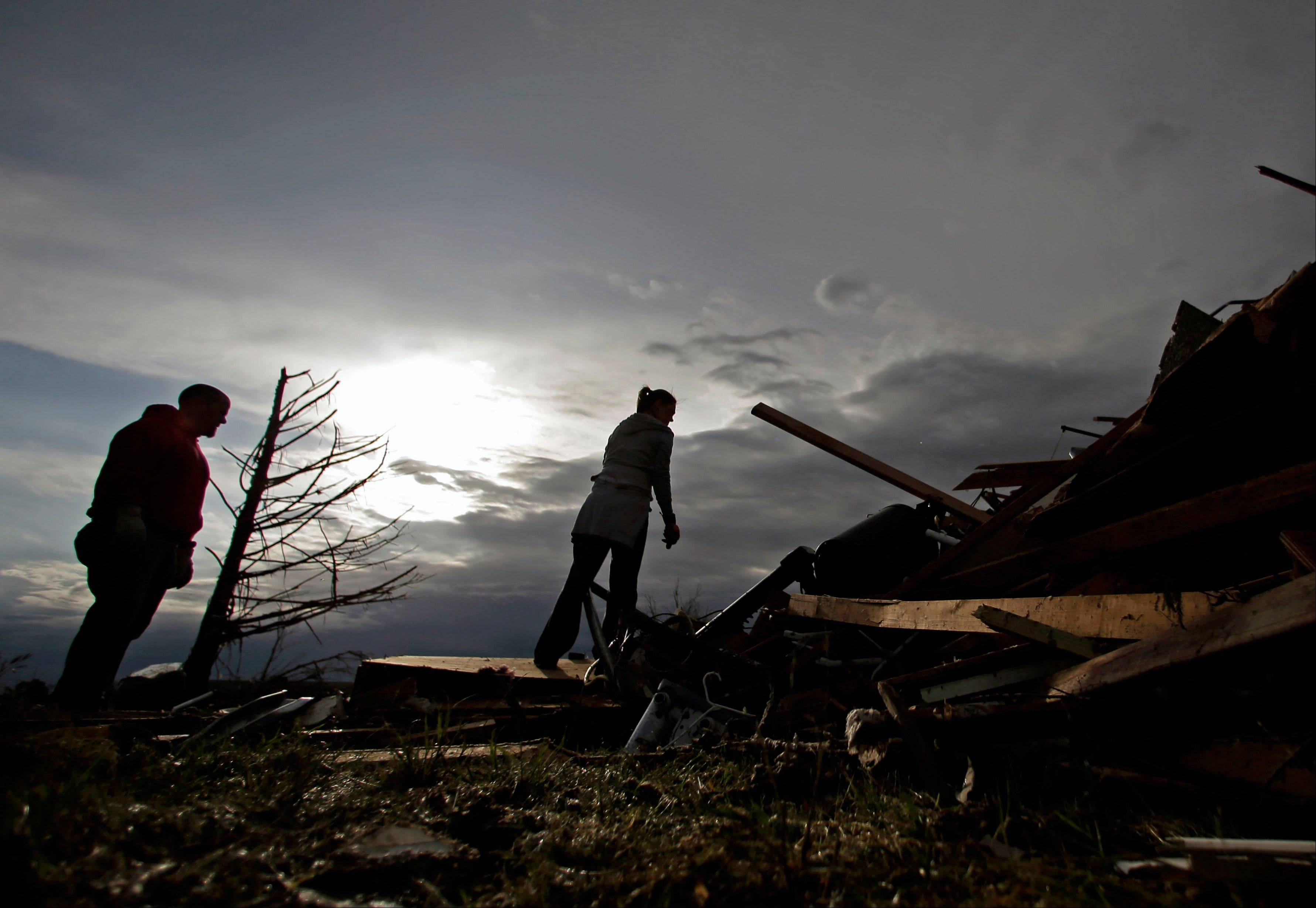 Zac and Denisha Woodcock look through the rubble of a tornado-ravaged rental home which they own Tuesday, May 21, 2013, in Moore, Okla. A huge tornado roared through the Oklahoma City suburb Monday, flattening an entire neighborhoods and destroying an elementary school with a direct blow as children and teachers huddled against winds.