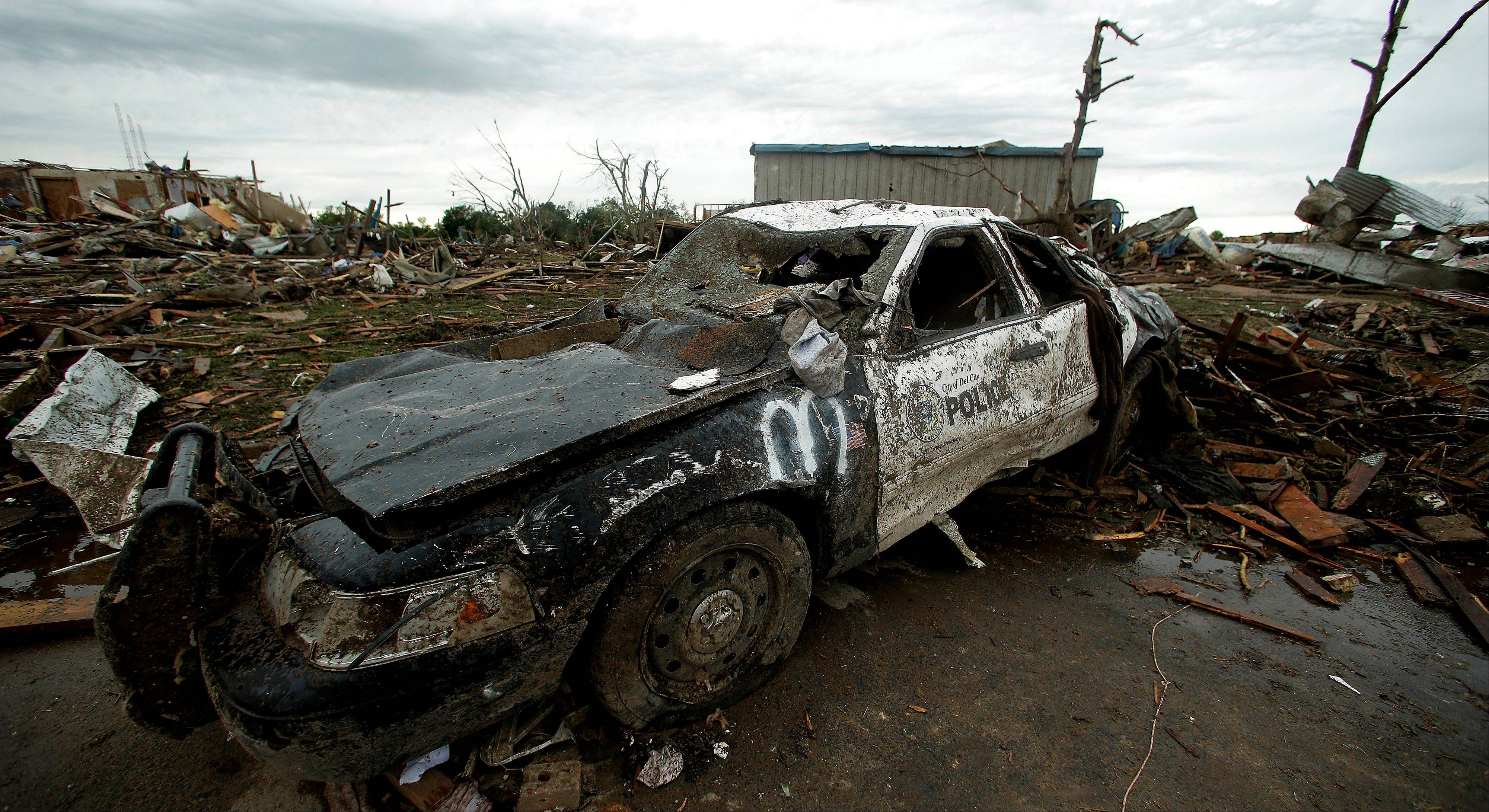 A destroyed police car sits among the debris of tornado-ravaged homes Tuesday, May 21, 2013, in Moore, Okla. A huge tornado roared through the Oklahoma City suburb Monday, flattening an entire neighborhoods and destroying an elementary school with a direct blow as children and teachers huddled against winds.