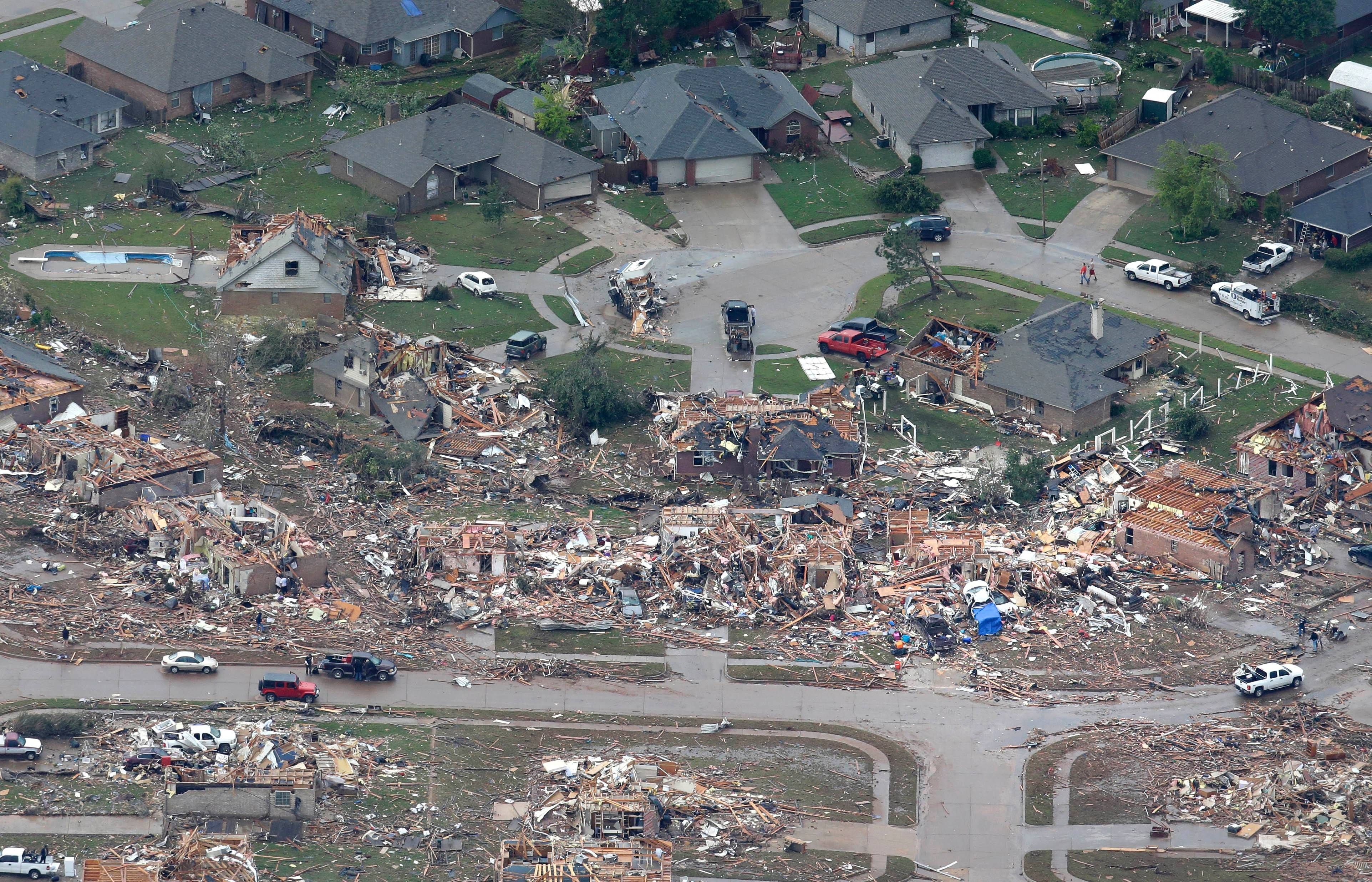 An aerial view shows homes damaged by Monday's tornado as others appear untouched, Tuesday, May 21, 2013, in Moore, Okla.  At least 24 people, including nine children, were killed in the massive tornado that flattened homes and a school in Moore, on Monday afternoon.