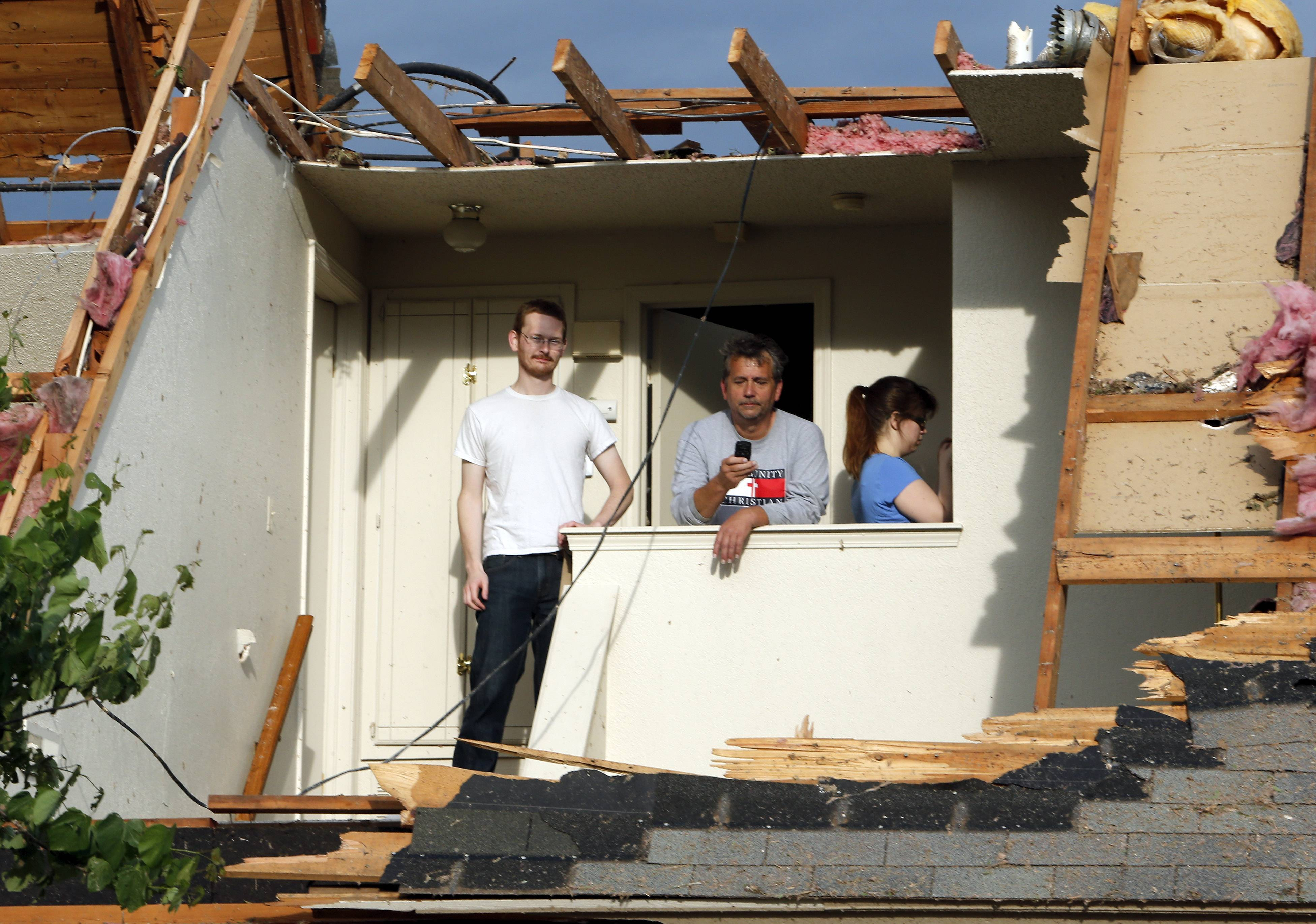 Brian Mullins and his Father Terry survey tornado damage to the home of Brian's girlfriend Sara Robinson, right, on Tuesday, May 21, 2013 in Moore, Okla.