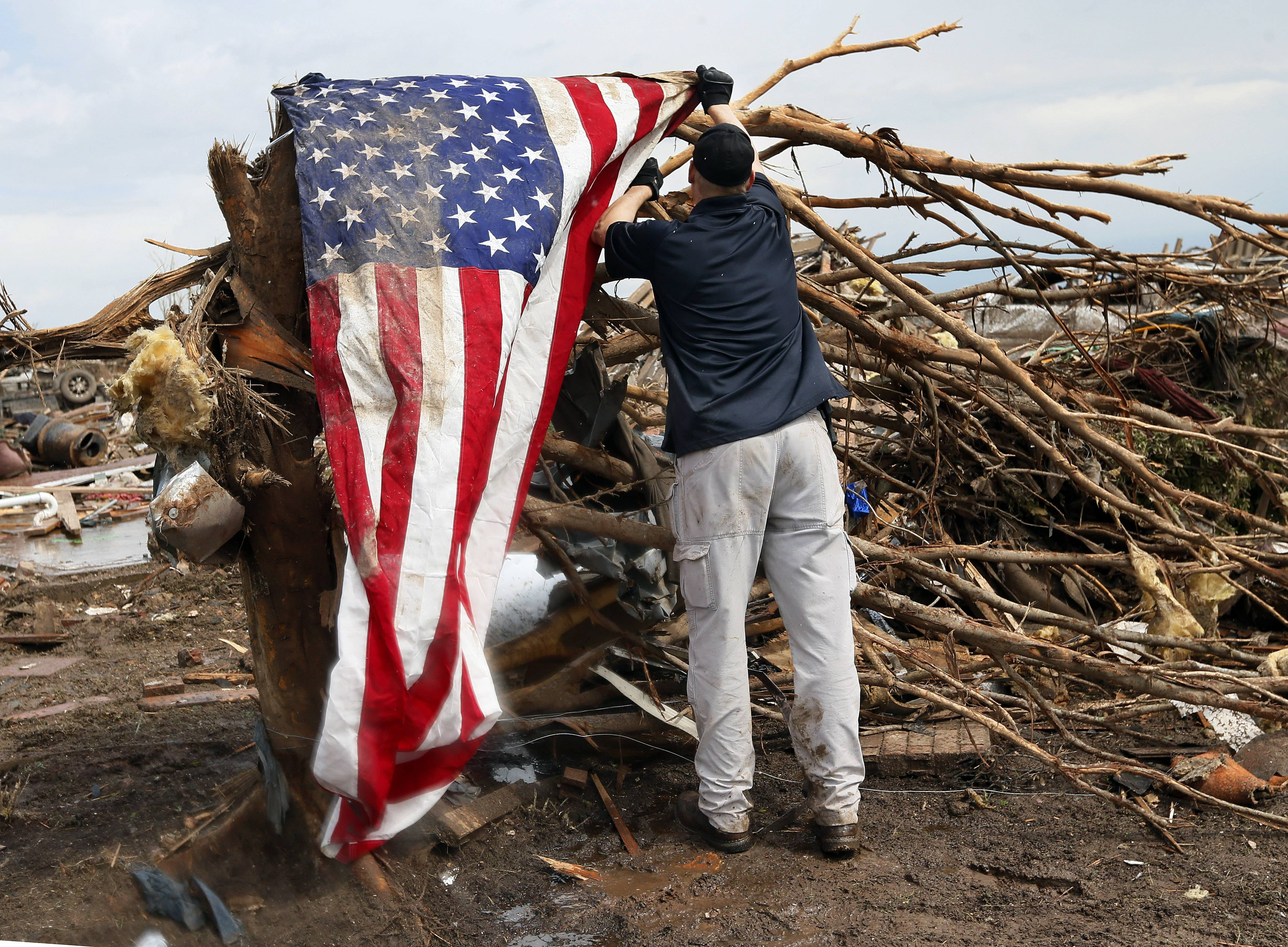 A man who asked not to be identified hangs an American flag on what is left of a tree in a neighborhood north of SW 149th between Western and Santa Fe on Tuesday, May 21, 2013, after a tornado struck south Oklahoma City and Moore, Okla., on Monday.