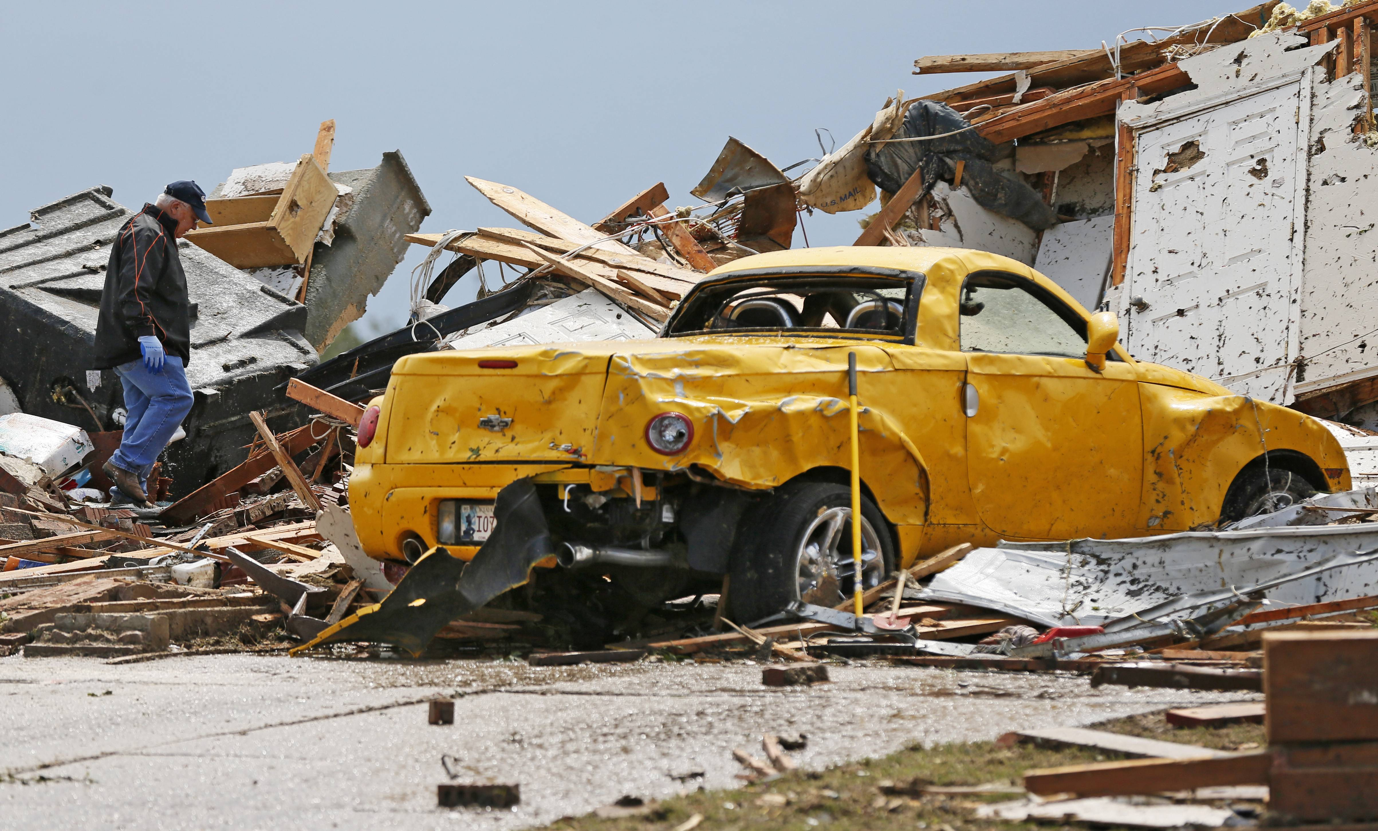 Hugh Harrell walks through debris near his 2005 Chevy SSR at the house of his daughter, Kaci Harrell, 14708 S. Broadway, in Oklahoma City on Tuesday, May 21, 2013, after a tornado struck south Oklahoma City and Moore, Okla., on Monday. Hugh Harrell had the car parked in his daughter's garage to protect it from hail.