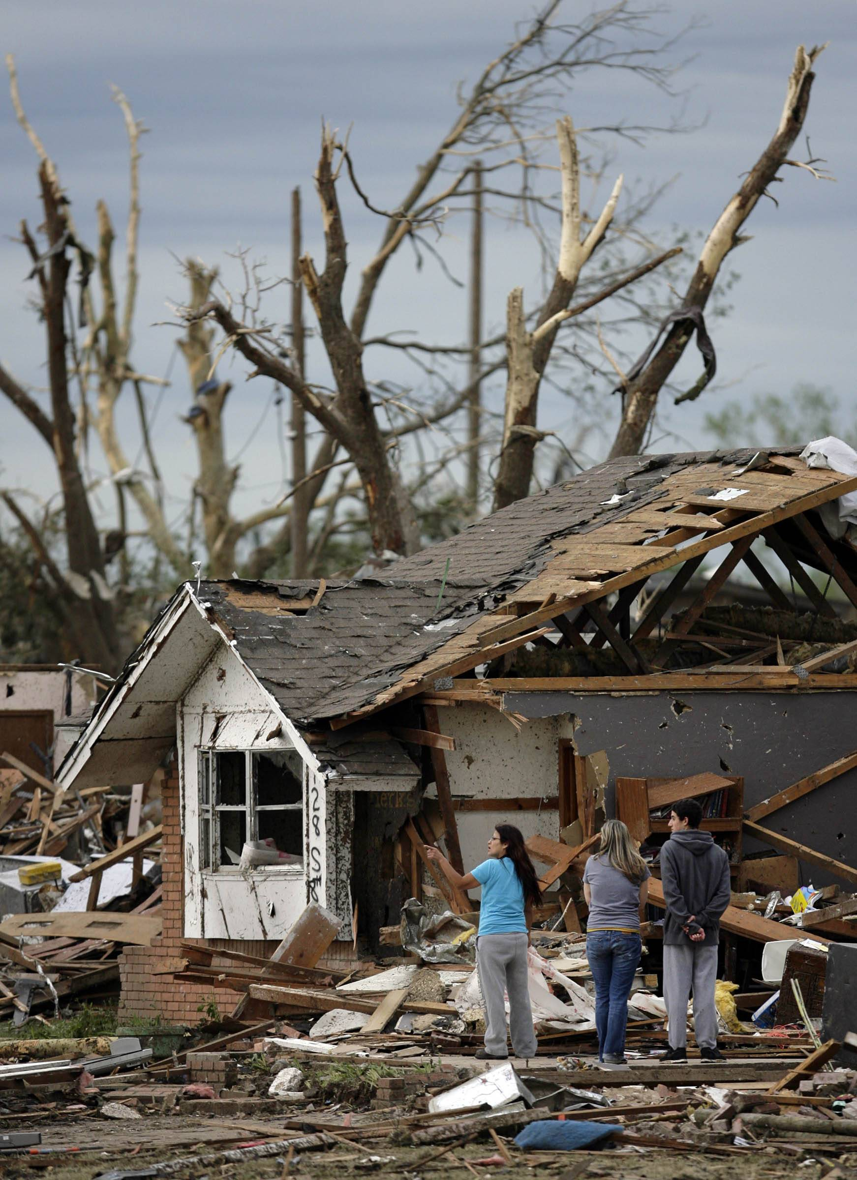 A family looks over their destroyed home in Moore, Okla. Tuesday, May 21, 2013. A huge tornado roared through the Oklahoma City suburb Monday, flattening entire neighborhoods and destroying an elementary school with a direct blow as children and teachers huddled against winds.