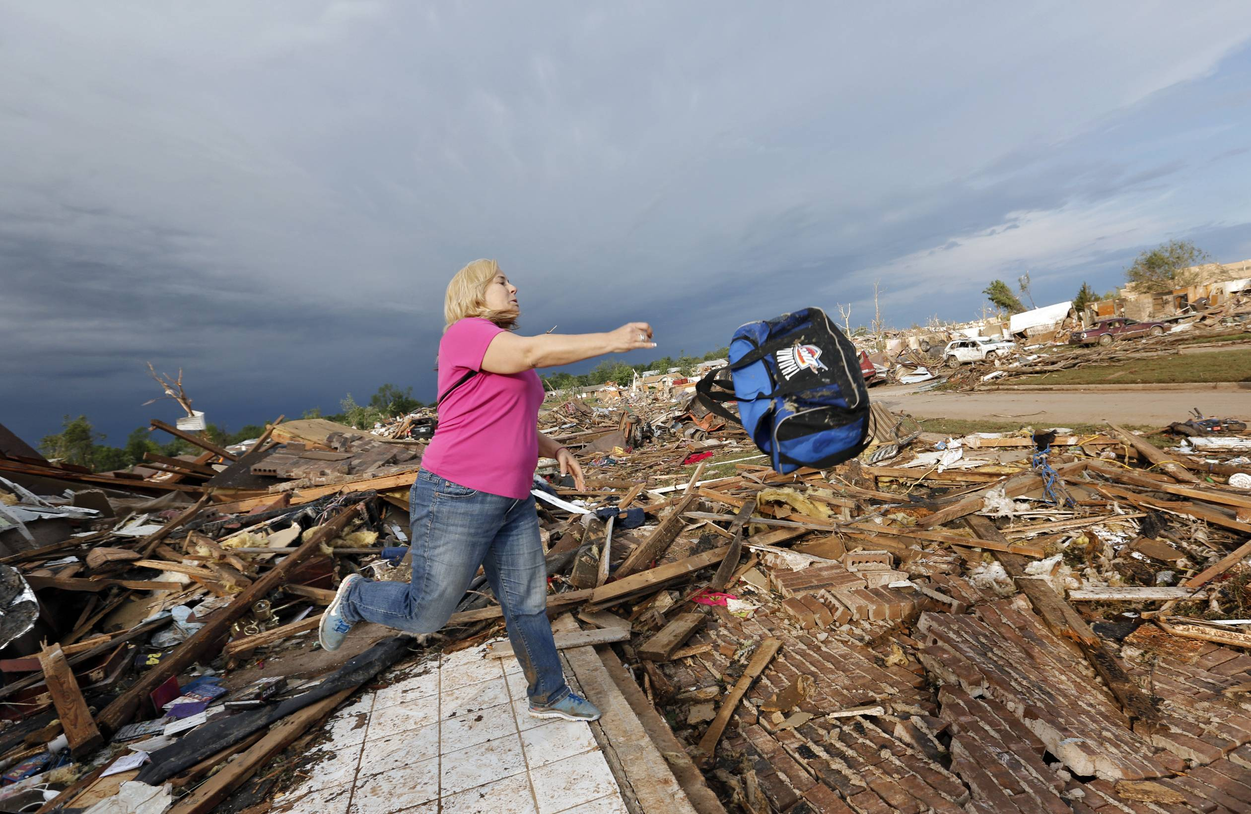 Penny Phillips throws out a bag of salvaged clothing as she goes through the remains of her home on Tuesday, May 21, 2013 in Moore, Okla. that was destroyed by Monday's tornado in the area near 4th and Bryant.