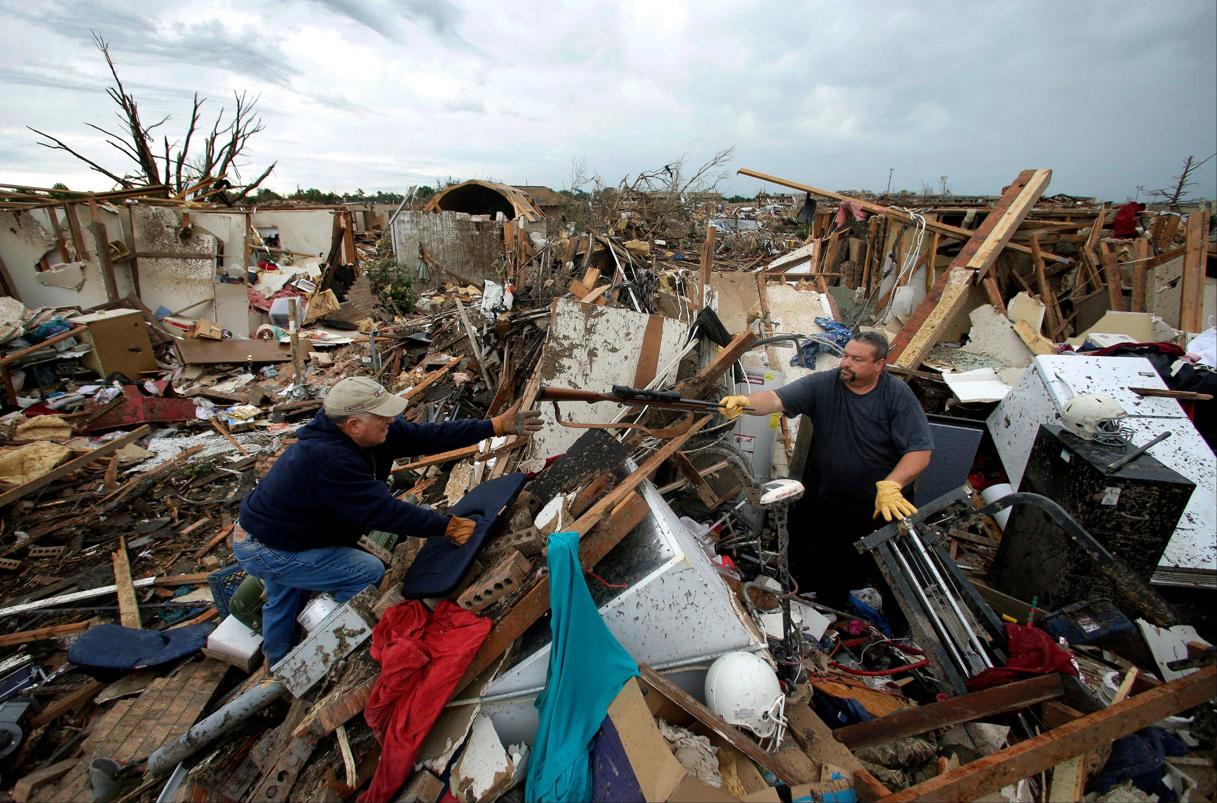 Dalton Sprading, right, hands a gun to his uncle Roger Craft as he salvages items from his tornado-ravaged home Tuesday, May 21, 2013, in Moore, Okla. A huge tornado roared through the Oklahoma City suburb Monday, flattening an entire neighborhoods and destroying an elementary school with a direct blow as children and teachers huddled against winds.