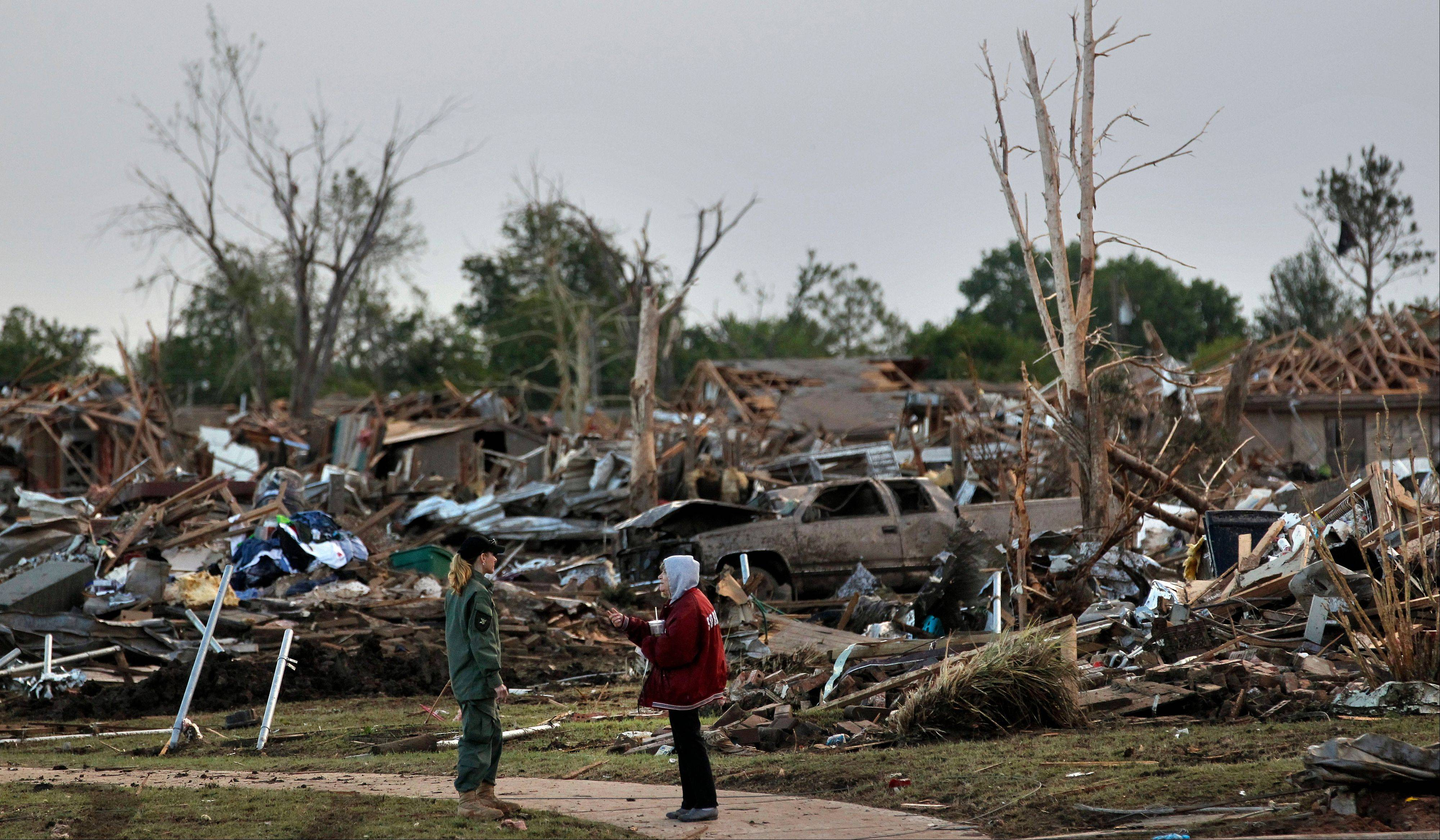 A member of a security team, left, talks with a local resident amid the rubble of destroyed homes, Tuesday May 21, 2013 in Moore, Okla. Monday a massive tornado moved through Moore, Okla., flattening entire neighborhoods.