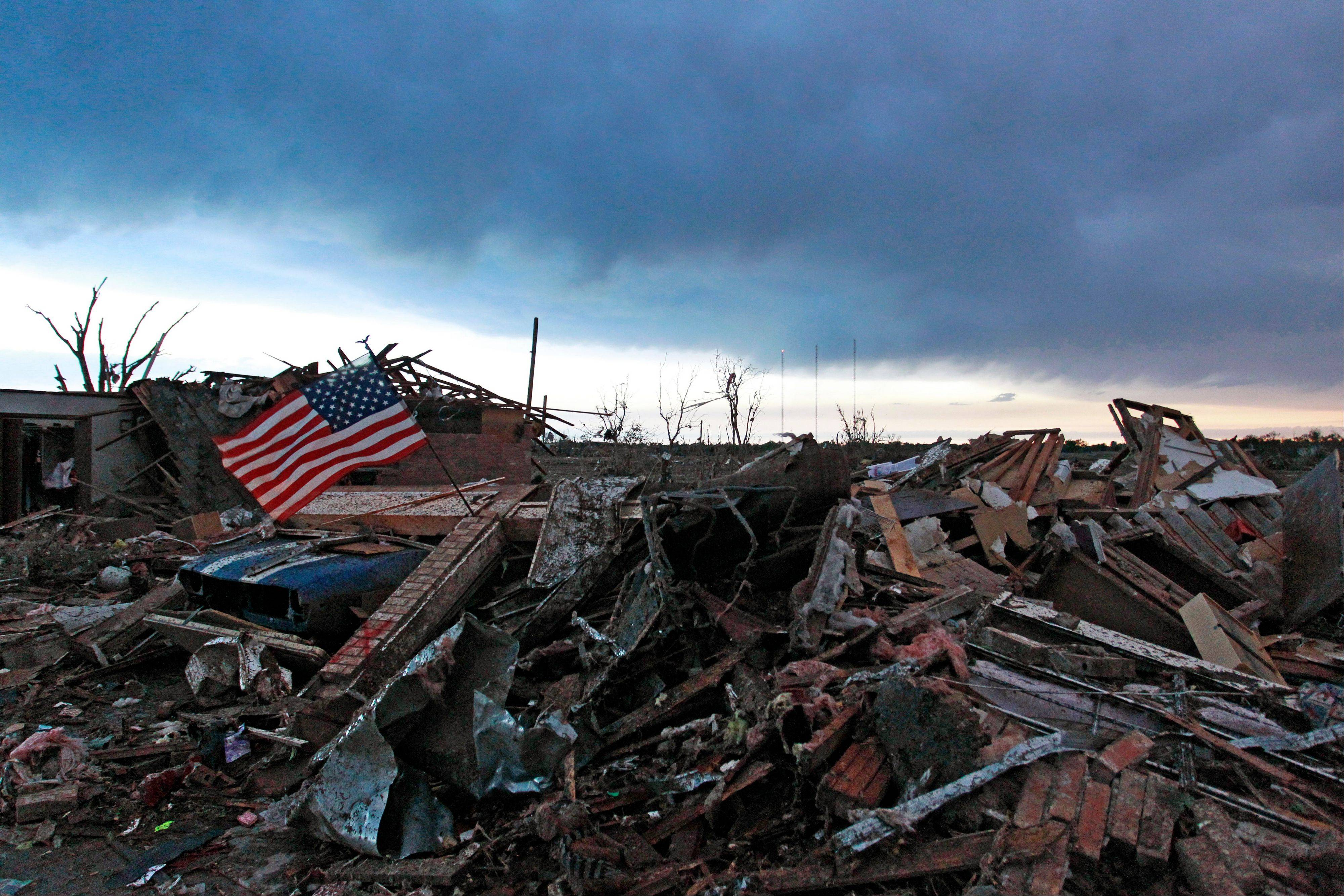An American flag blows in the wind at sunrise atop the rubble of a destroyed home a day after a tornado moved through Moore, Okla., Tuesday, May 21, 2013. The monstrous tornado roared through the Oklahoma City suburb Monday, flattening entire neighborhoods and destroying an elementary school with a direct blow as children and teachers huddled against winds up to 200 mph.