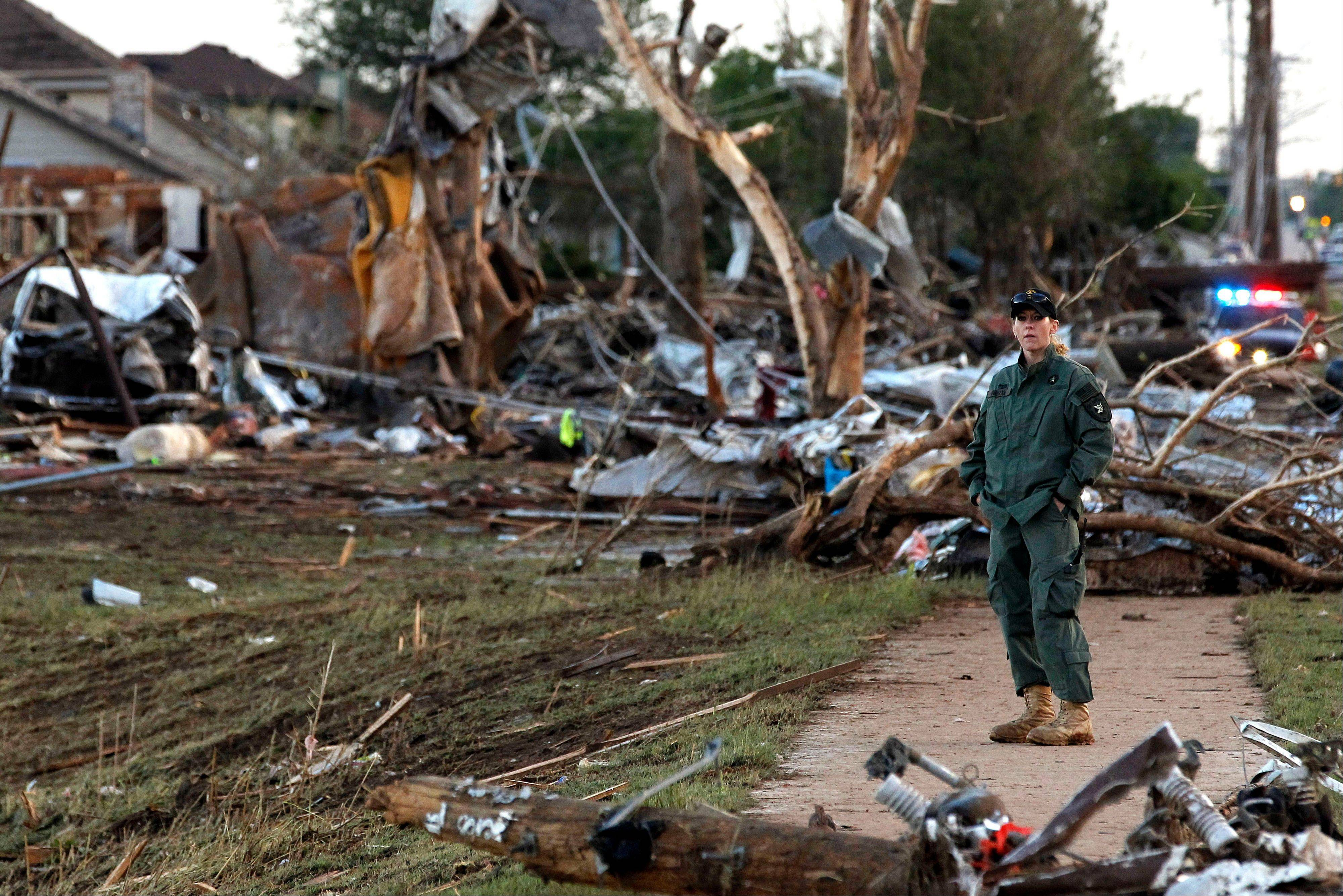 A member of a security team helps guard an area of rubble from a destroyed residential neighborhood, one day after a tornado moved through Moore, Okla., Tuesday, May 21, 2013. The huge tornado roared through the Oklahoma City suburb Monday, flattening entire neighborhoods and destroying an elementary school with a direct blow as children and teachers huddled against the winds.