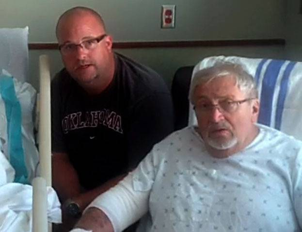 Schaumburg Trustee Frank Kozak, right, with his son Steve, from an Oklahoma hospital room tells how a water heater and wall fell on top of him, possibly saving his life.