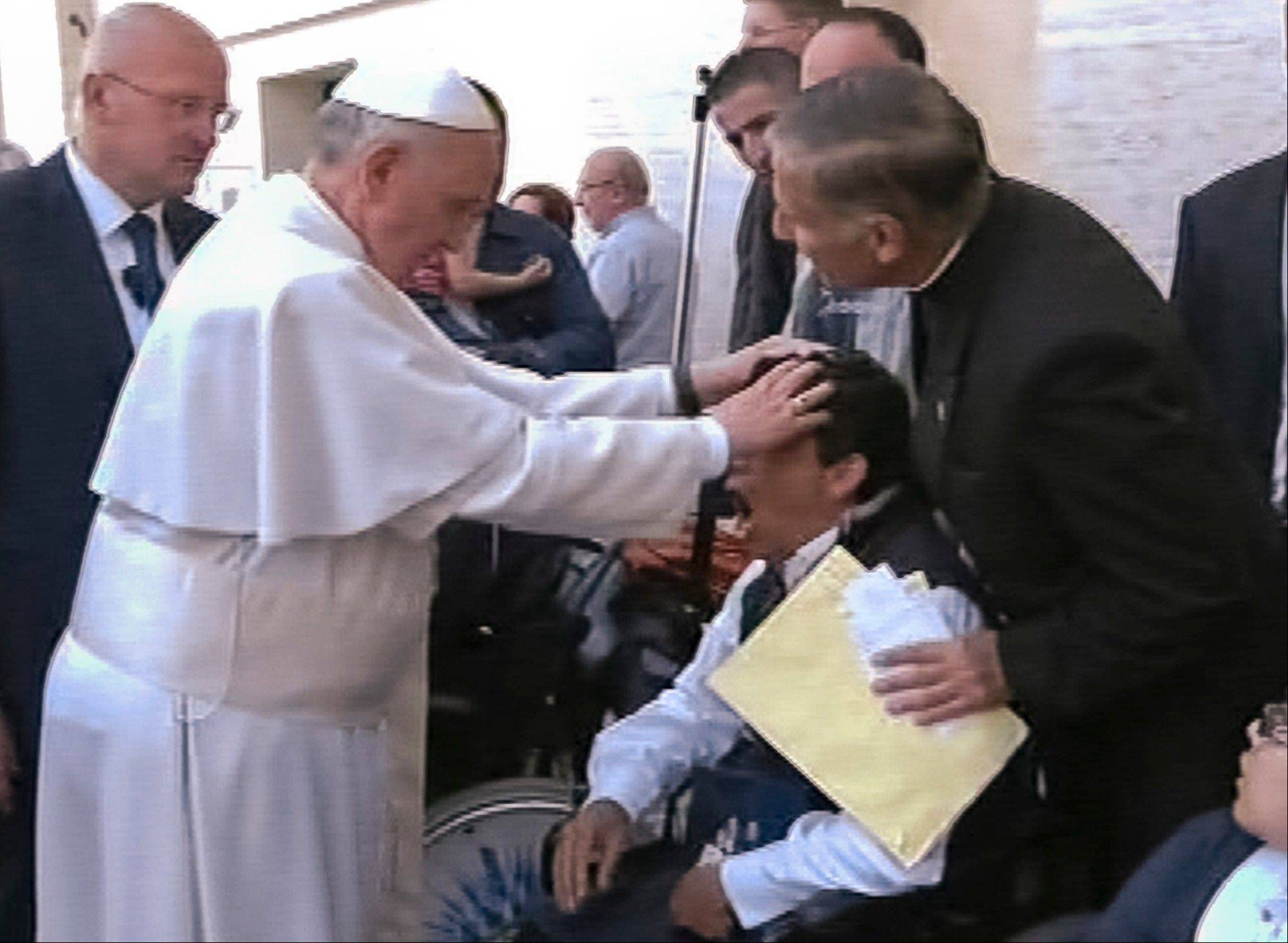 In this image made from video provided by APTN, Pope Francis lays his hands on the head of a young man on Sunday, May 19, 2013, after celebrating Mass in St. Peter's Square. The young man heaved deeply a half-dozen times, convulsed and shook, and then slumped in his wheelchair as Francis prayed over him. The television station of the Italian bishops' conference said it had surveyed exorcists, who agreed Francis either performed an exorcism or a prayer to free the man from the devil. The Vatican was more cautious Tuesday, saying Francis �didn�t intend to perform any exorcism. But as he often does for the sick or suffering, he simply intended to pray for someone.