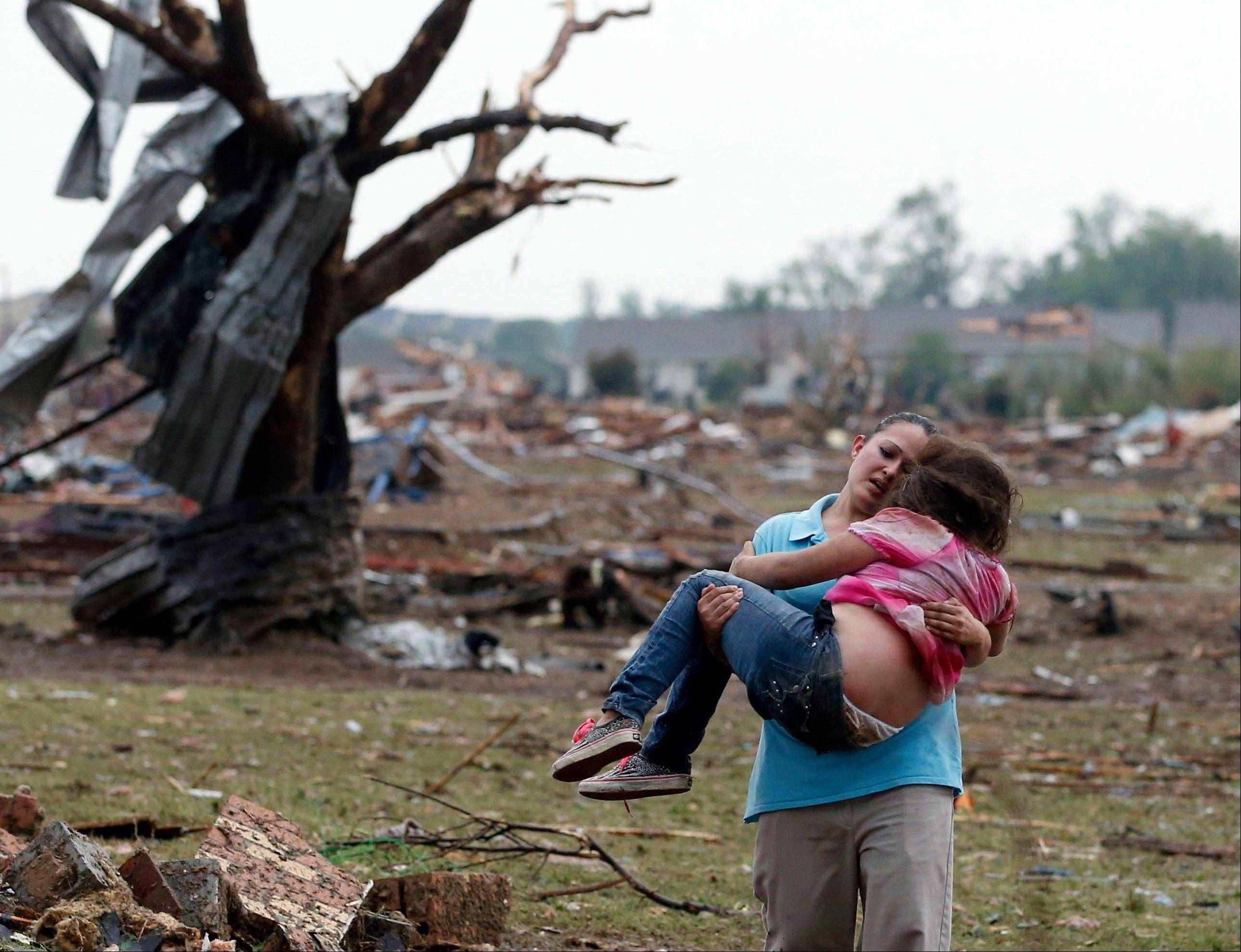 A woman carries a child through a field near the collapsed Plaza Towers Elementary School in Moore, Okla., Monday, May 20, 2013.
