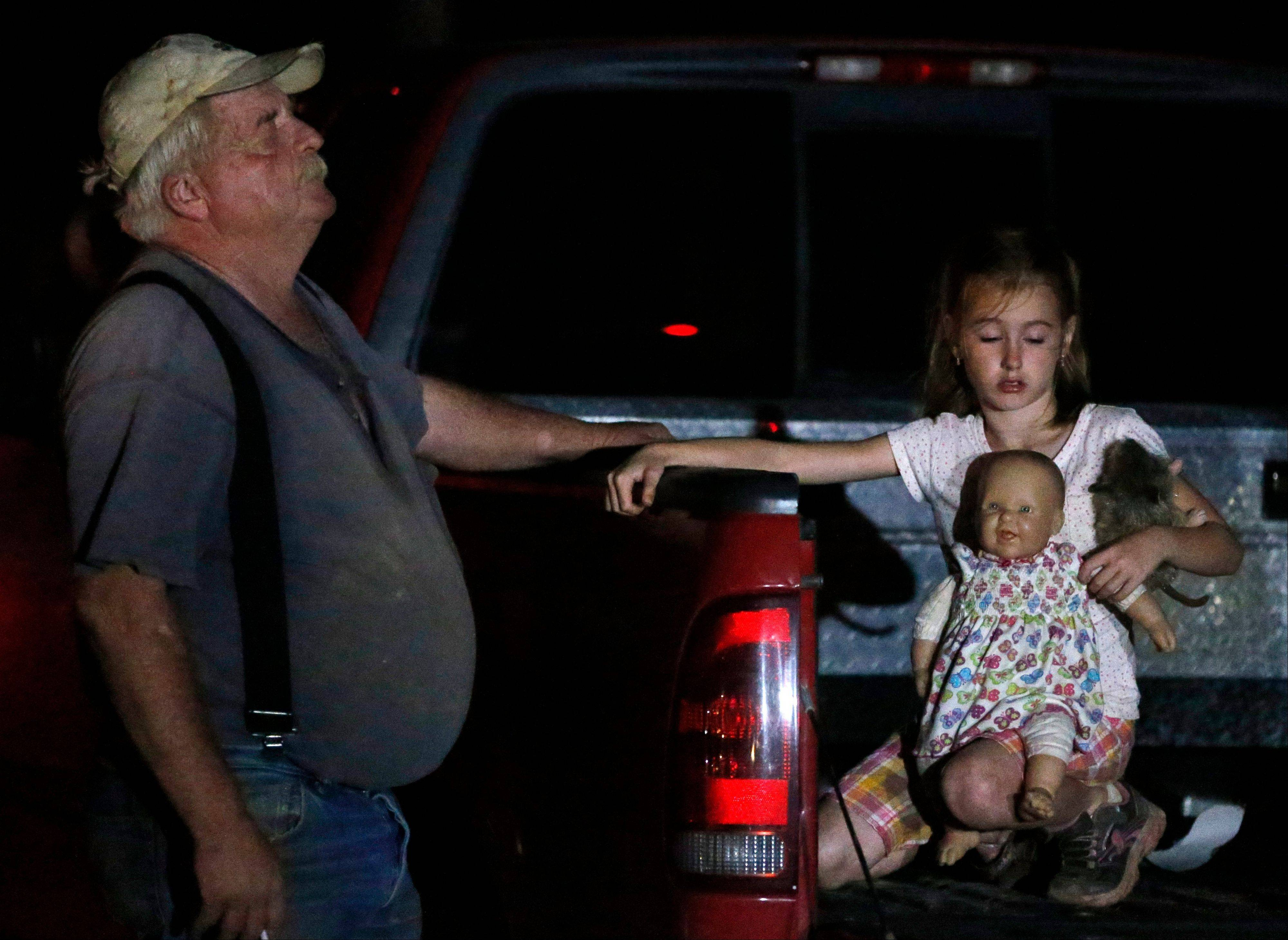 Seven-year-old Katrina Ash, right, holds a doll as she waits in the back of a truck with her grandfather, Michael Bowen, left, after a tornado ripped through their neighborhood near Dale, Okla., Monday, May 19, 2013.