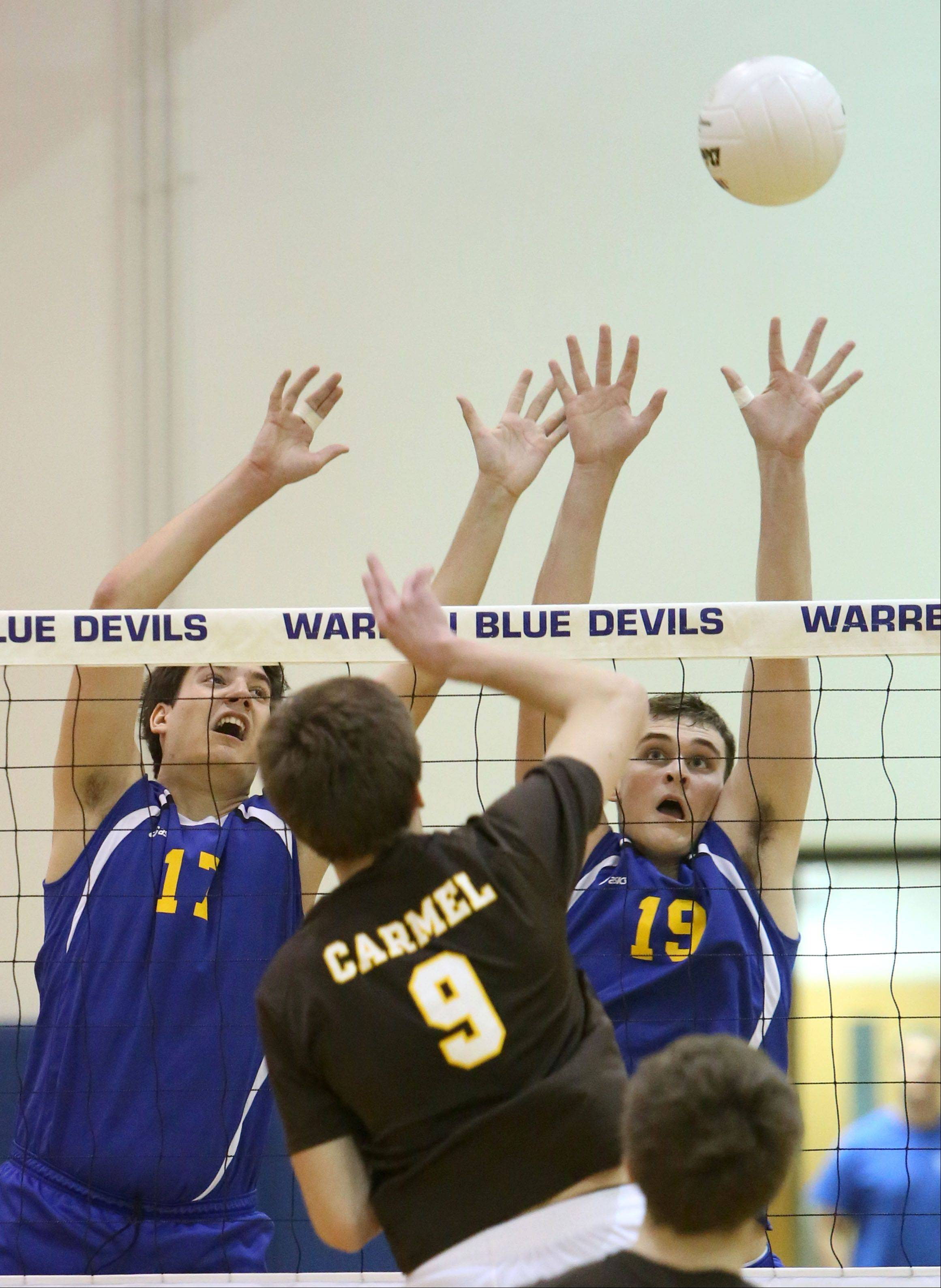 Carmel's Derek Clement, middle, spikes one at Warren's Vuk Jakovljevic and Max Bongratz during regional semifinal play Tuesday night at Warren.