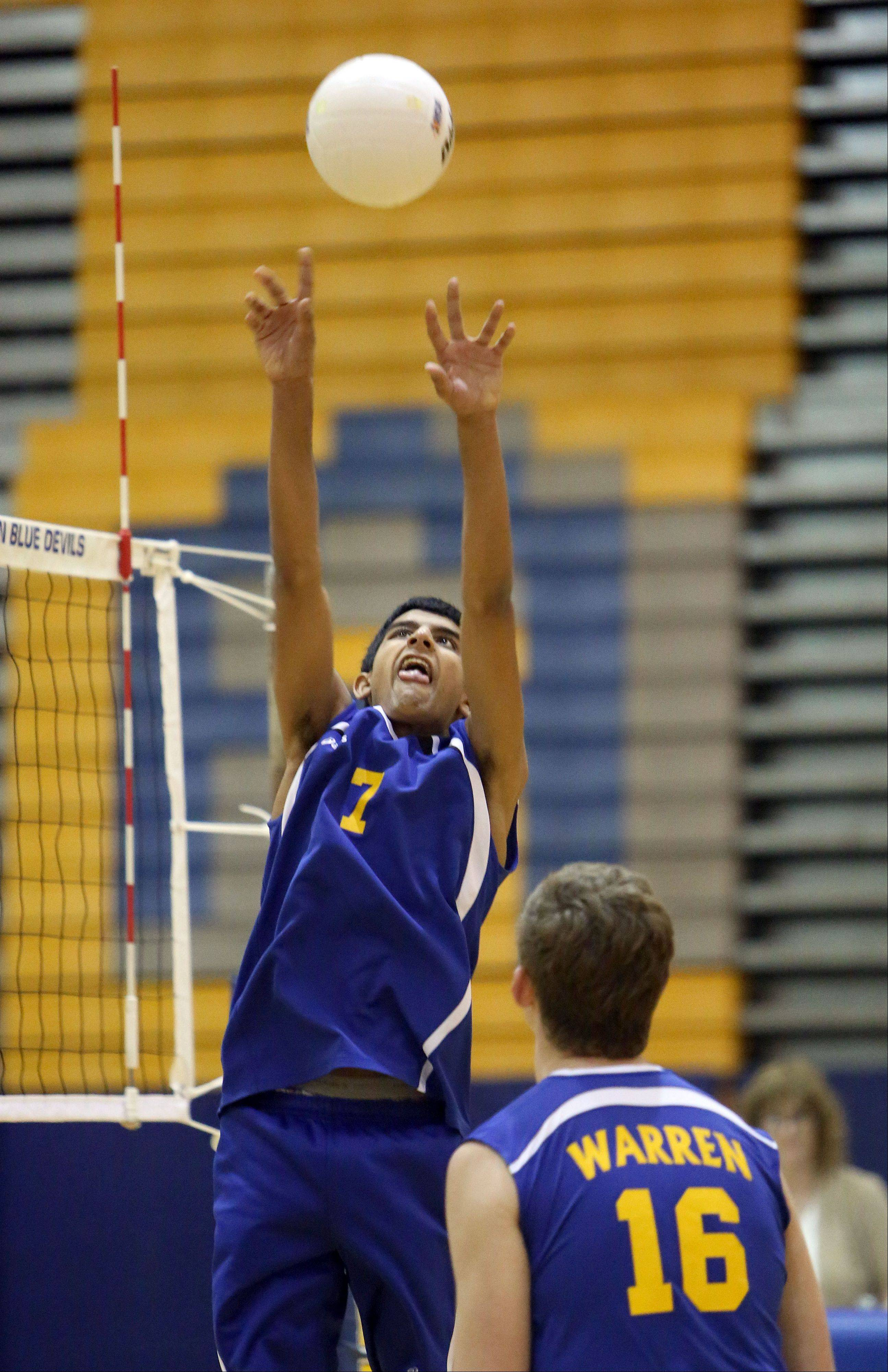 Warren's Arvind Kouta sets the ball to teammate Mitch Maan de Kok during regional semifinal play against Carmel on Tuesday night at Warren.
