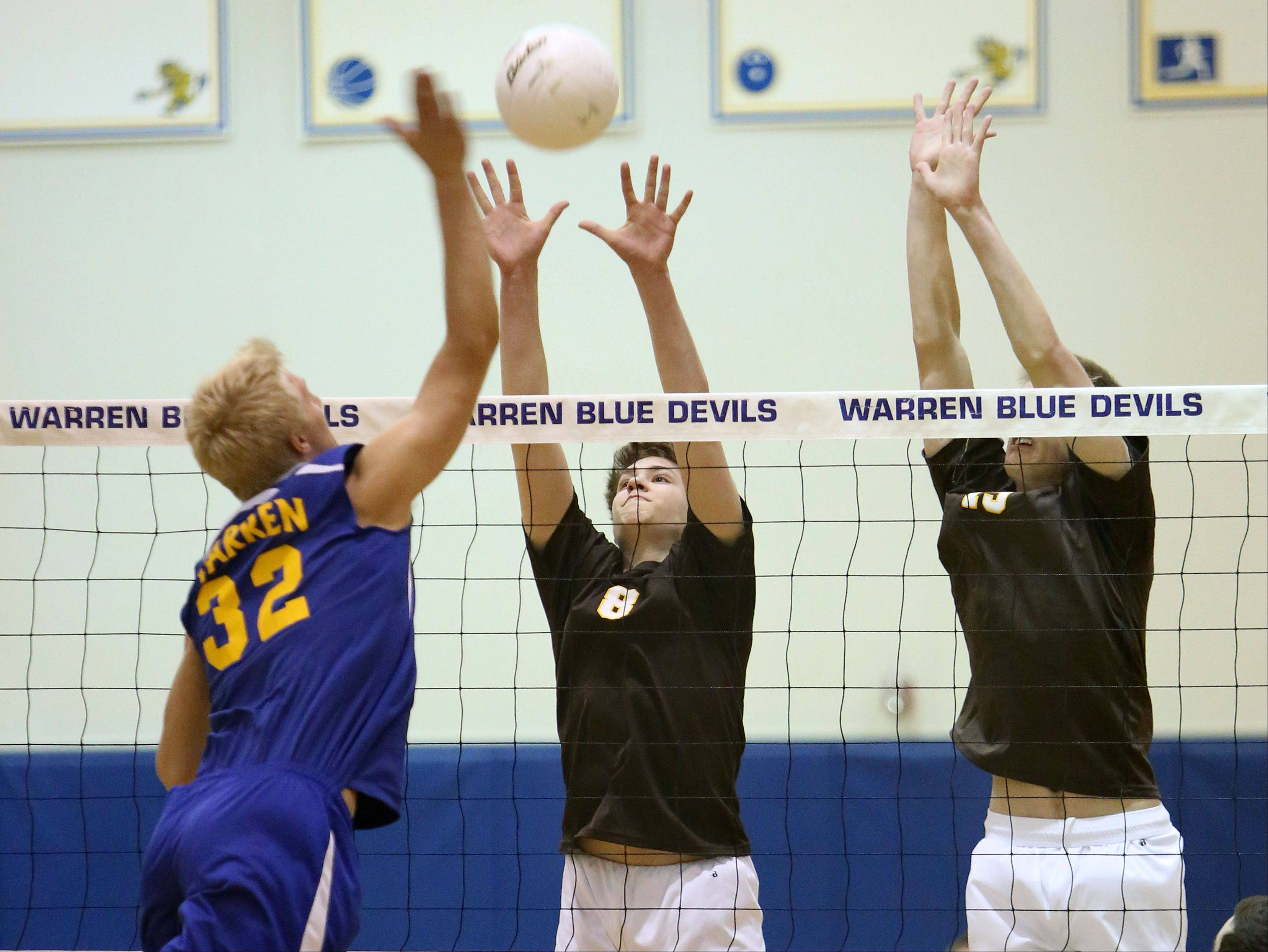 Warren's Zachary Schultz, left, spikes one at Carmel's Andrew Wloch and Brad Gadek during regional semifinal play Tuesday night at Warren.
