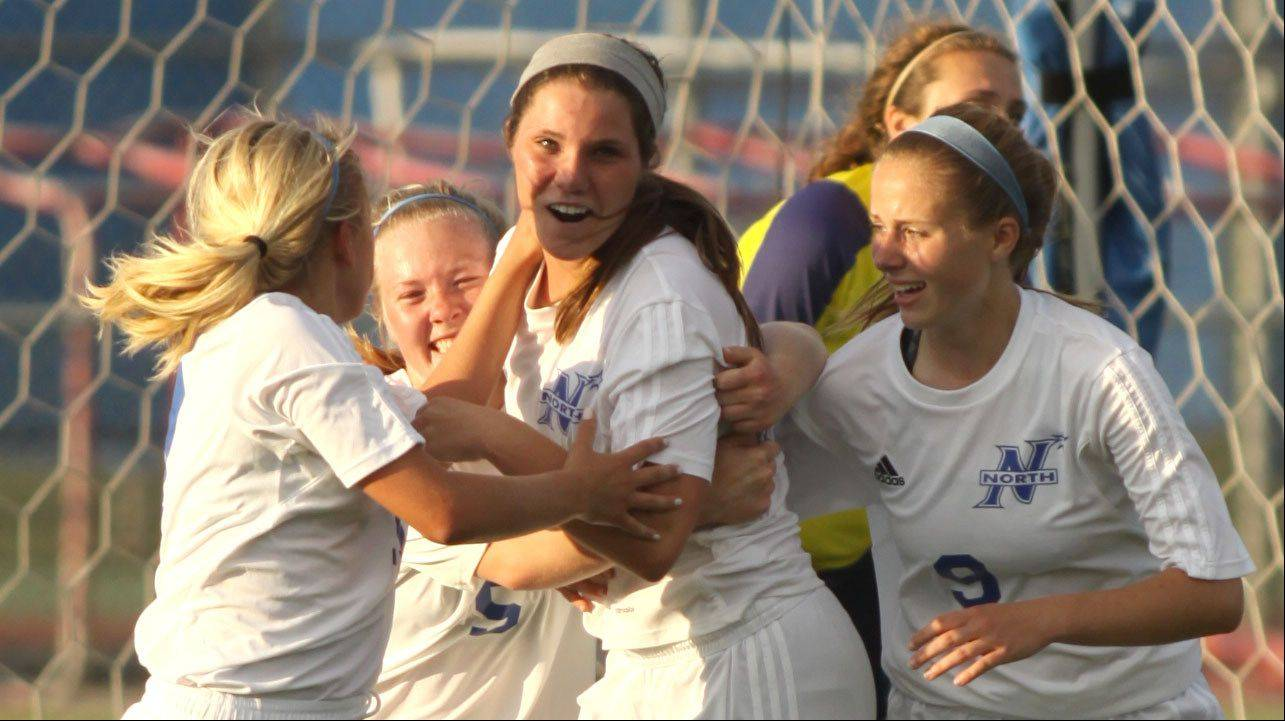 St Charles North players celebrate after a goal by Kenzie Rose, center, in the second overtime against Conant in sectional semifinal play at Hoffman Estates on Tuesday.