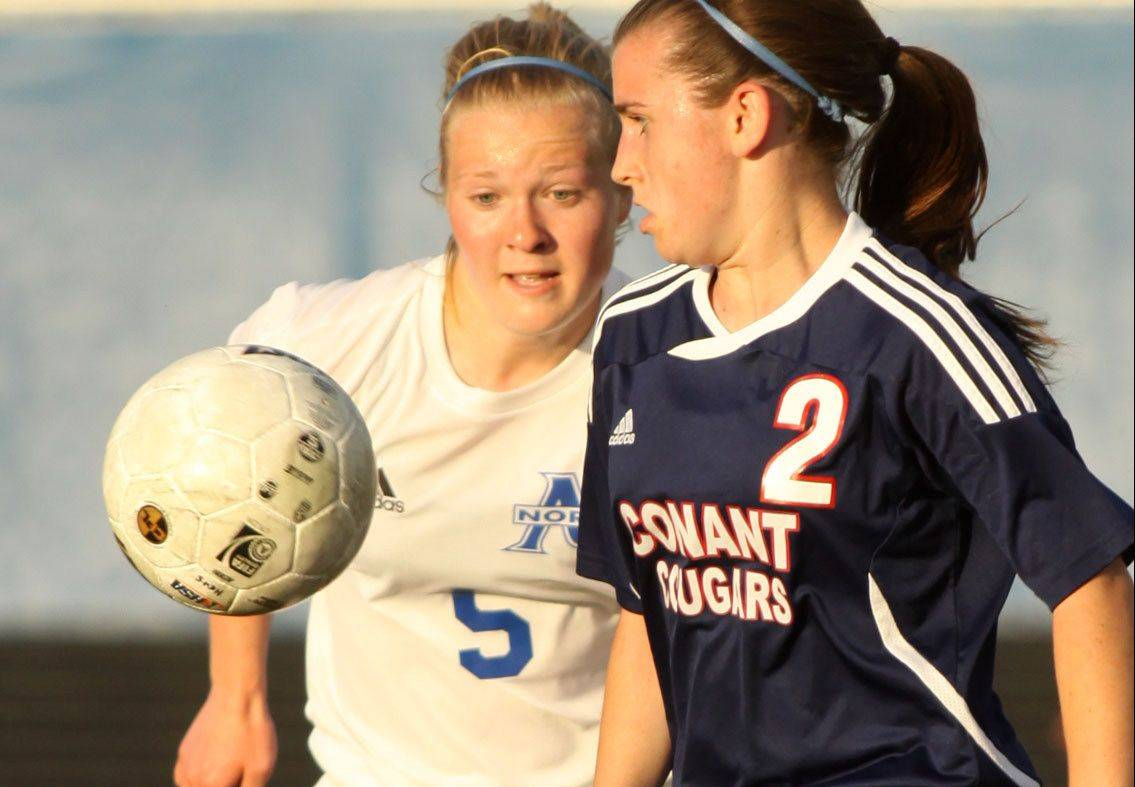 St Charles North's Natalie Winkates, left, battles Conant's Sidney O'Keeffe in sectional semifinal play at Hoffman Estates on Tuesday.