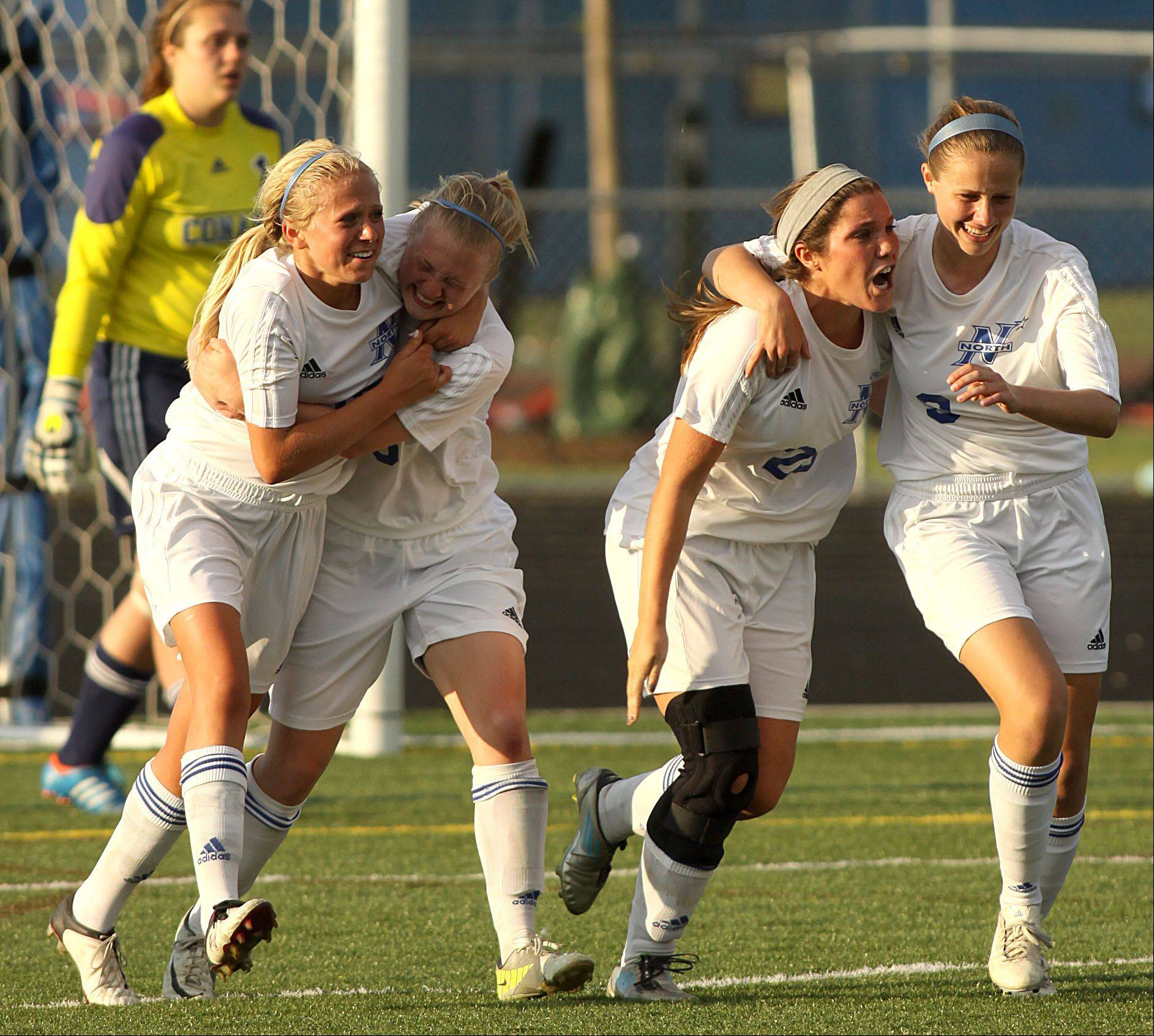St Charles North players celebrate after a goal by Kenzie Rose in the second overtime against Conant in sectional semifinal play at Hoffman Estates on Tuesday.