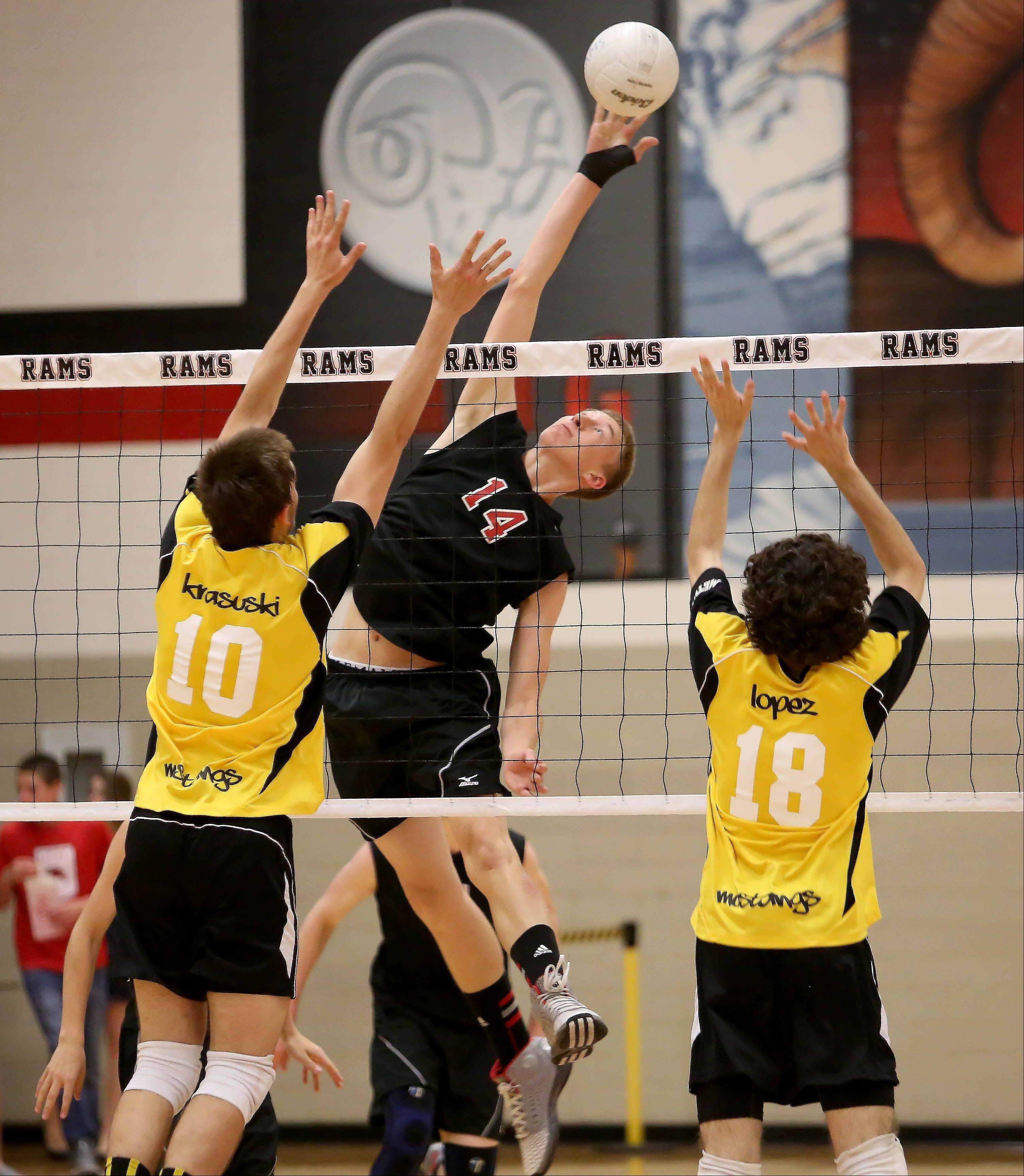 Dan Carlson of Glenbard East reaches up for the ball in boys regional volleyball action against Metea Valley in Lombard in Tuesday.