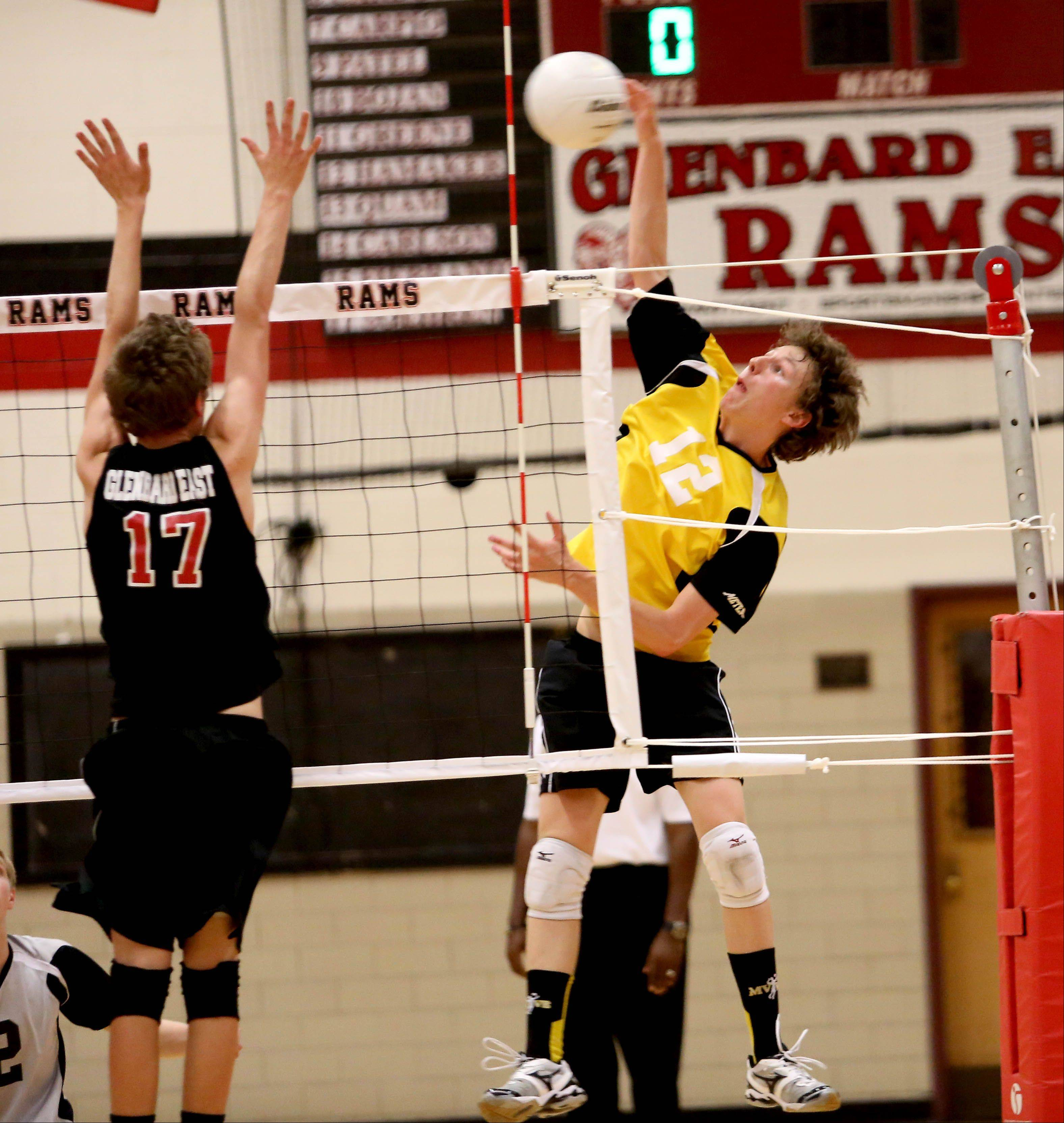 Ryan Luckinbill of Metea Valley spikes the ball in action against Glenbard East during boys regional volleyball in Lombard in Tuesday.