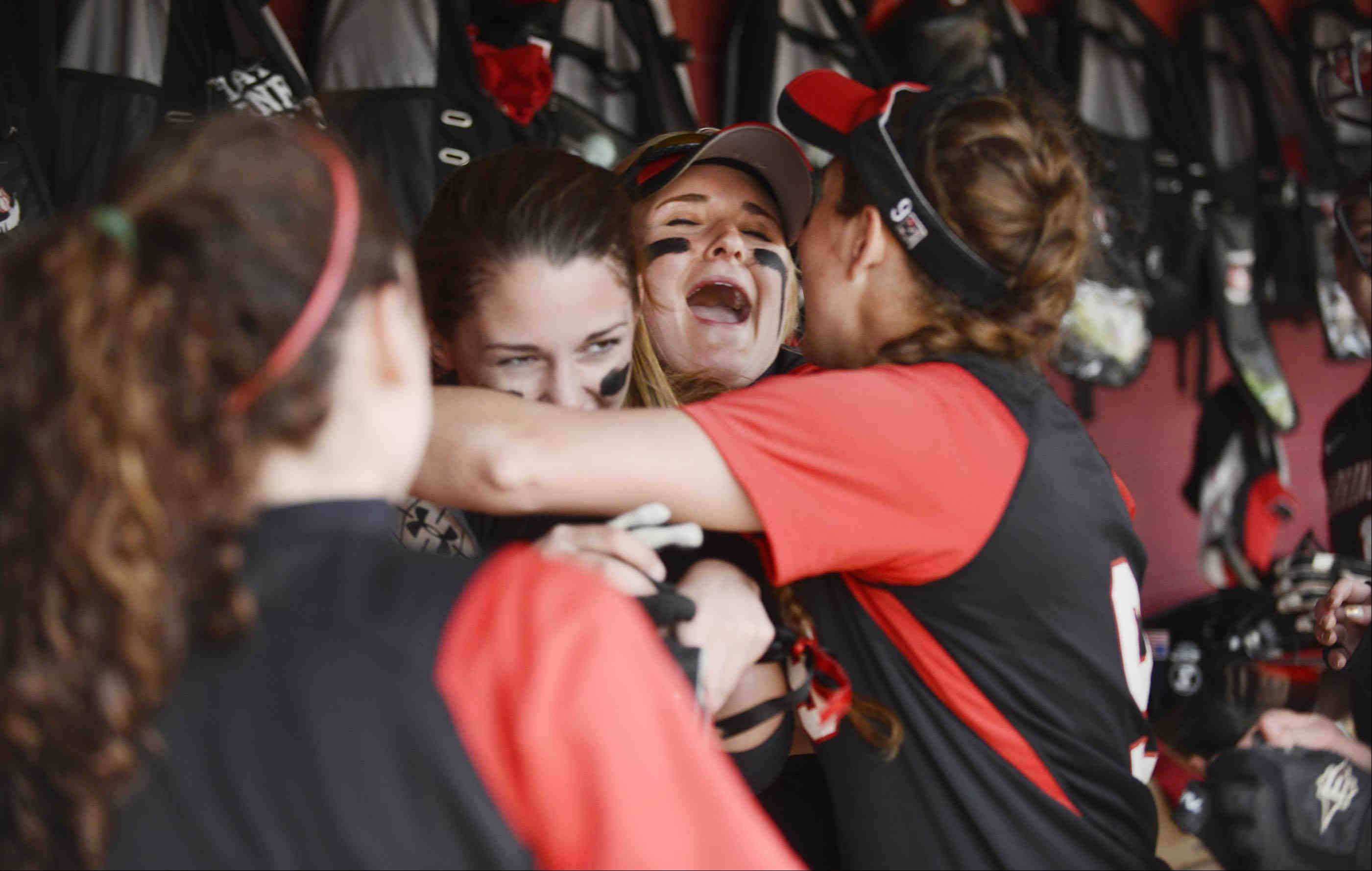 Barrington's Morgan Olszewski yells in the dugout as she and Maggie Ohara hug winning pitcher Keenan Dolezal after defeating Fremd Monday to win the MSL championship in Barrington.