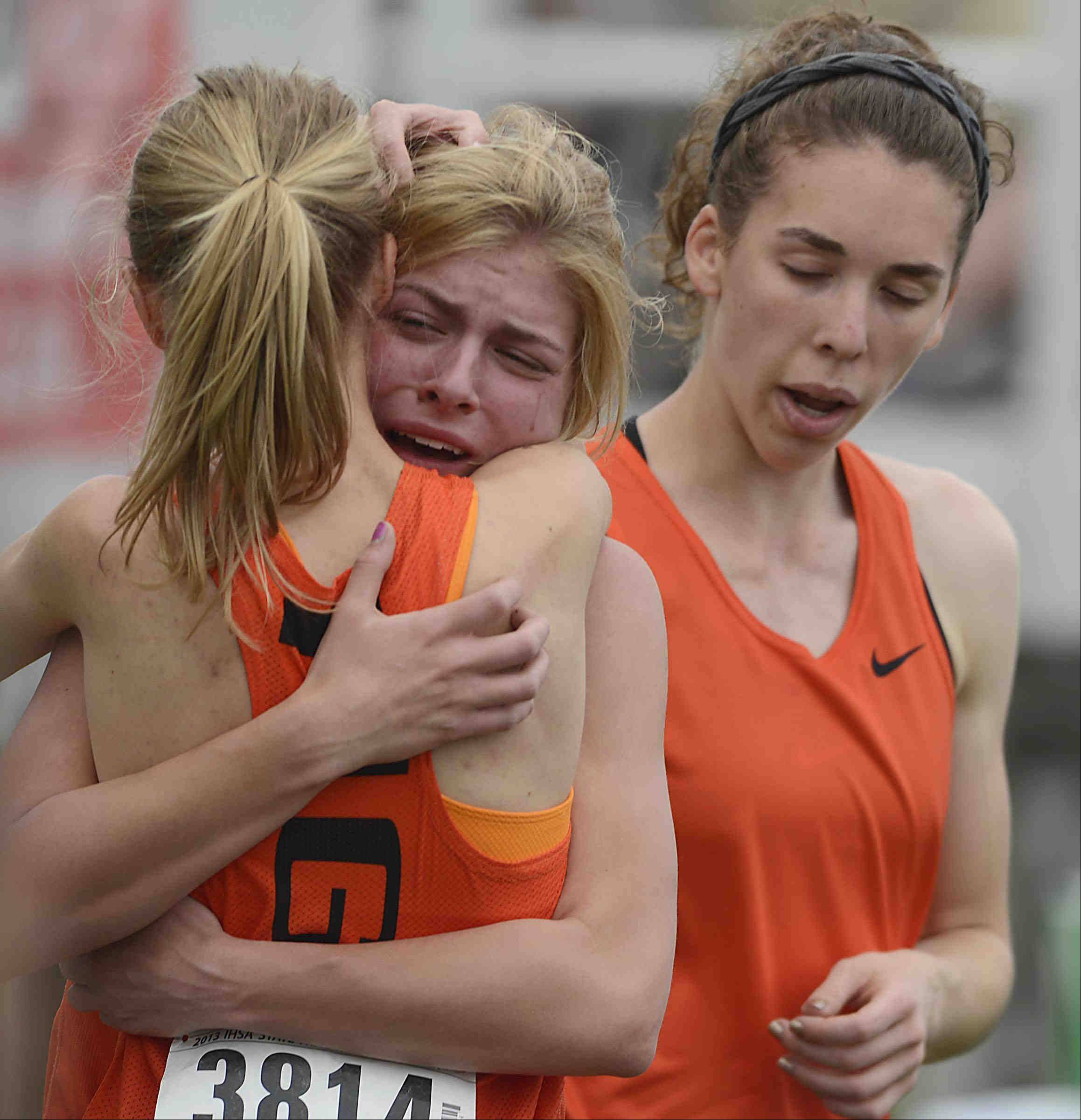 Wheaton Warrenville South's Emma Dalan cries and hugs 1,600 meter relay teammate Helen Majer as leadoff runner Jessica Spera joins them Friday at the Class 3A girls state track and field preliminaries at O'Brien Stadium at Eastern Illinois University in Charleston. Dalan fell and dropped the baton as she approached Majer for the handoff.