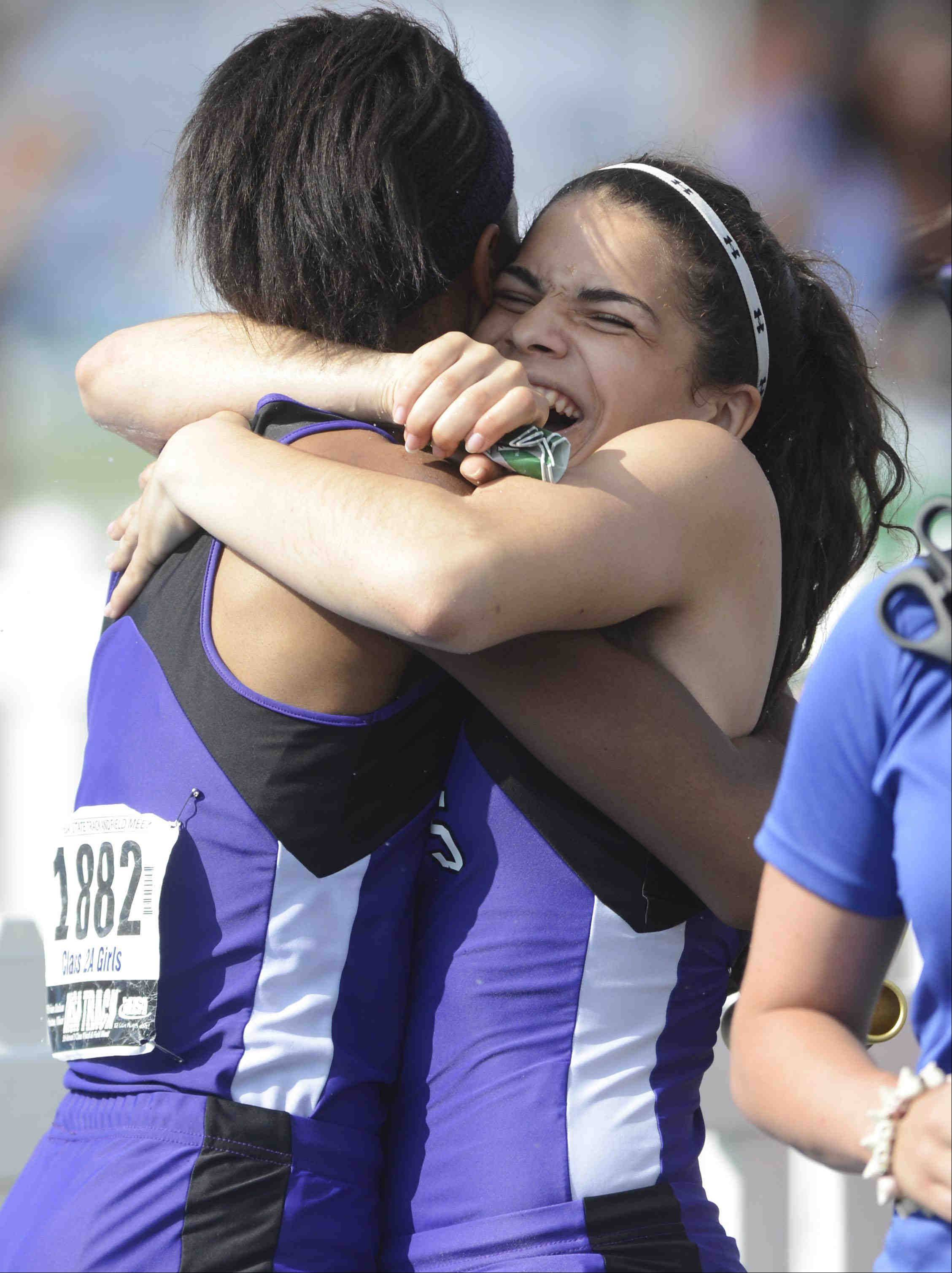 Hampshire's Elizabeth Pagan hugs teammate Ashley Fouch after their third place finish in the 1,600 meter relay Saturday at the Class 2A girls state track and field finals in Charleston.