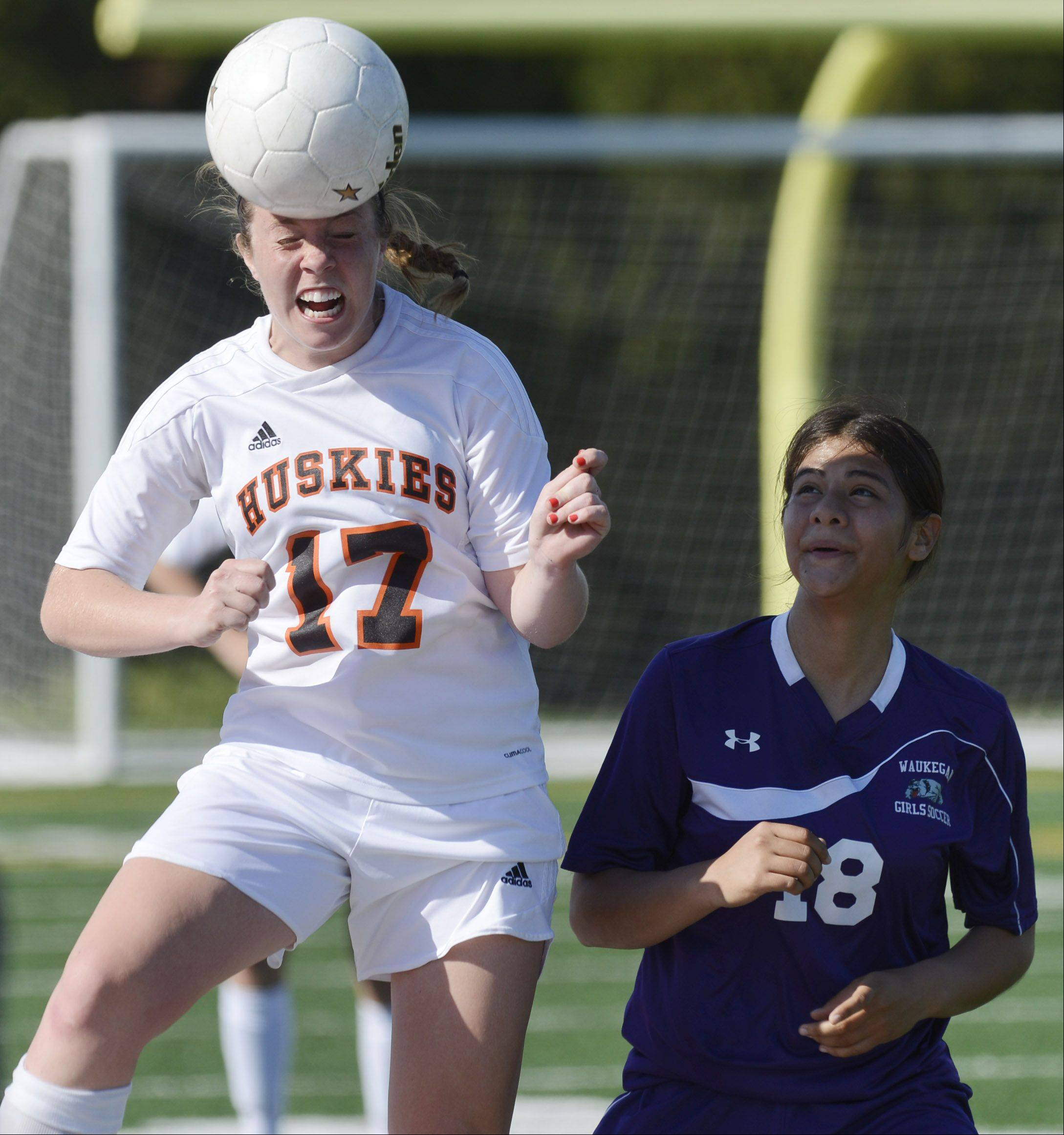 Hersey's Lauren Gierman, left, leaps for a header next to Waukegan's Jasmine Res.