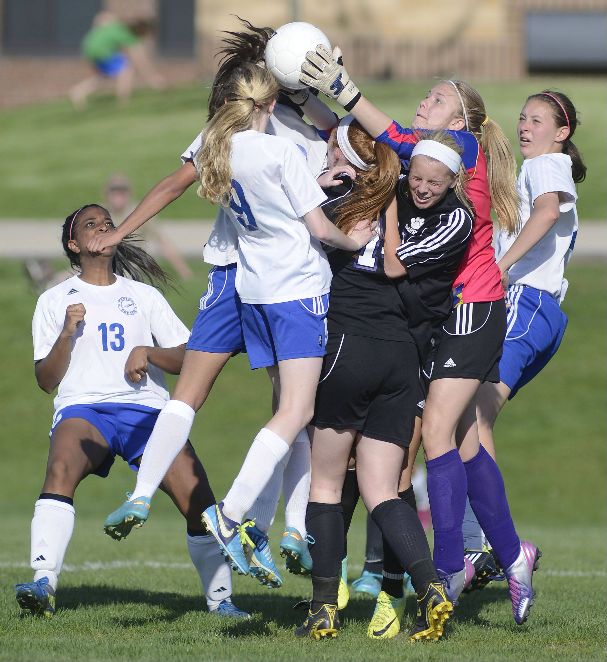 Burlington Central's Cali Andrew, 9, collides with Hampshire's Jessica Boutin and Paige Palubicki as Hampshire goalie Arianna Rominski leaps for the ball during Tuesday's Class 2A regional soccer semifinal.