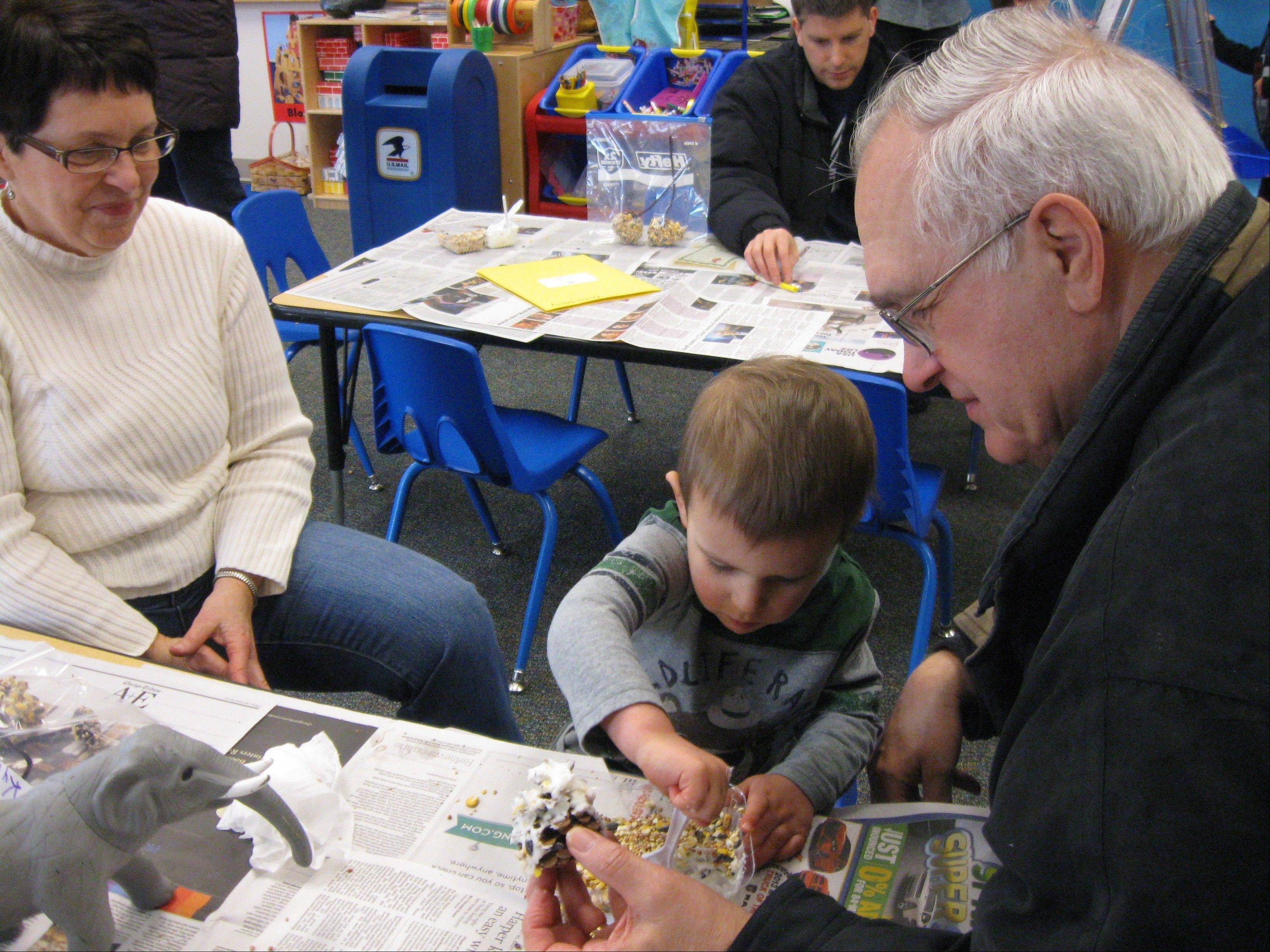 Grandparents and their grandson make a pine cone bird feeder at the Leave No Child Inside initiative sponsored by Citizens for Conservation and Noah's Ark Preschool.
