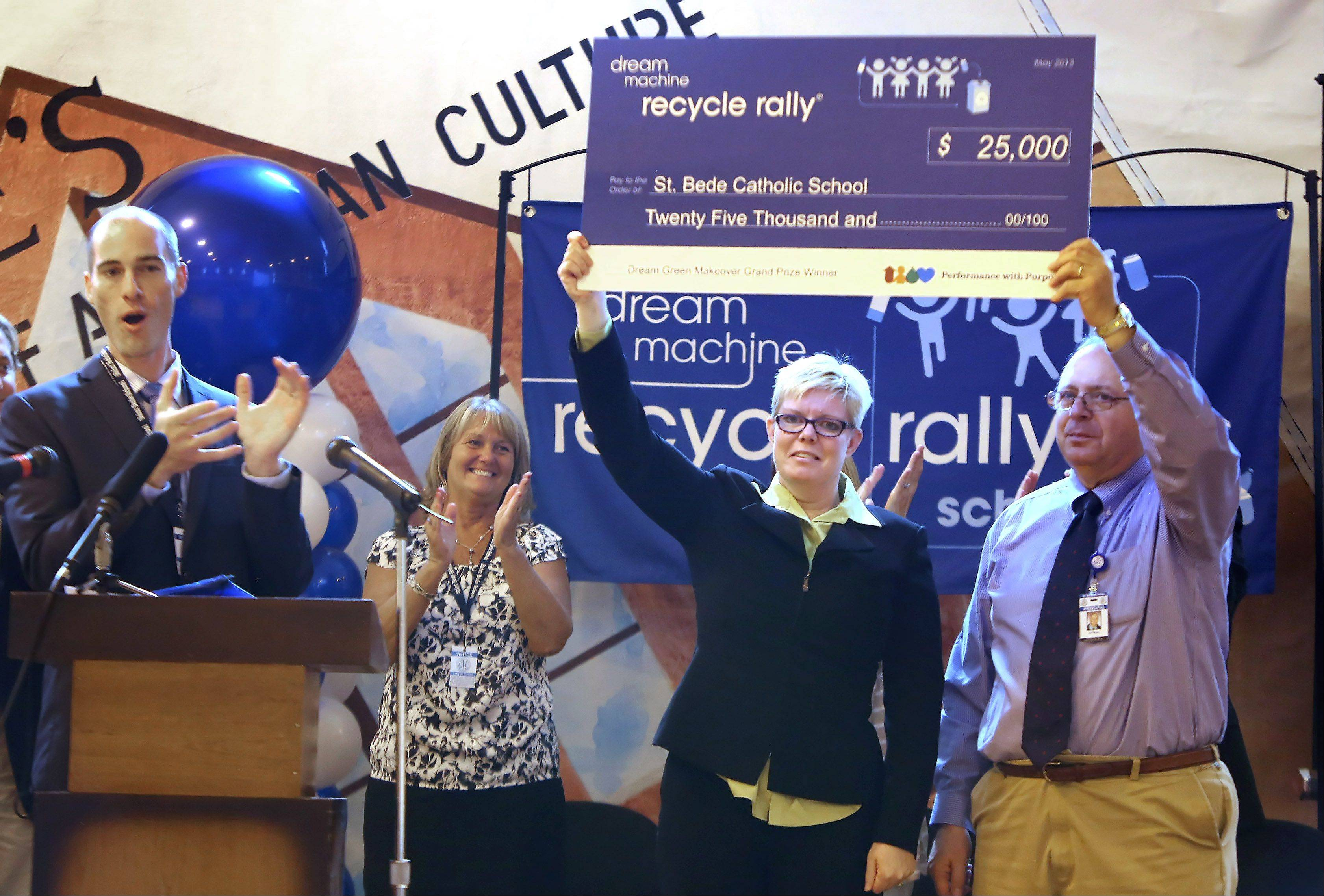 PepsiCo executive Tom Mooradian, left, applauds after handing a $25,000 check to St. Bede Catholic School PTA President Gretchen Renlund and Principal Charles Pinto during a celebration Wednesday. The Ingleside school won a grand prize in the Dream Machine Recycle Rally program.
