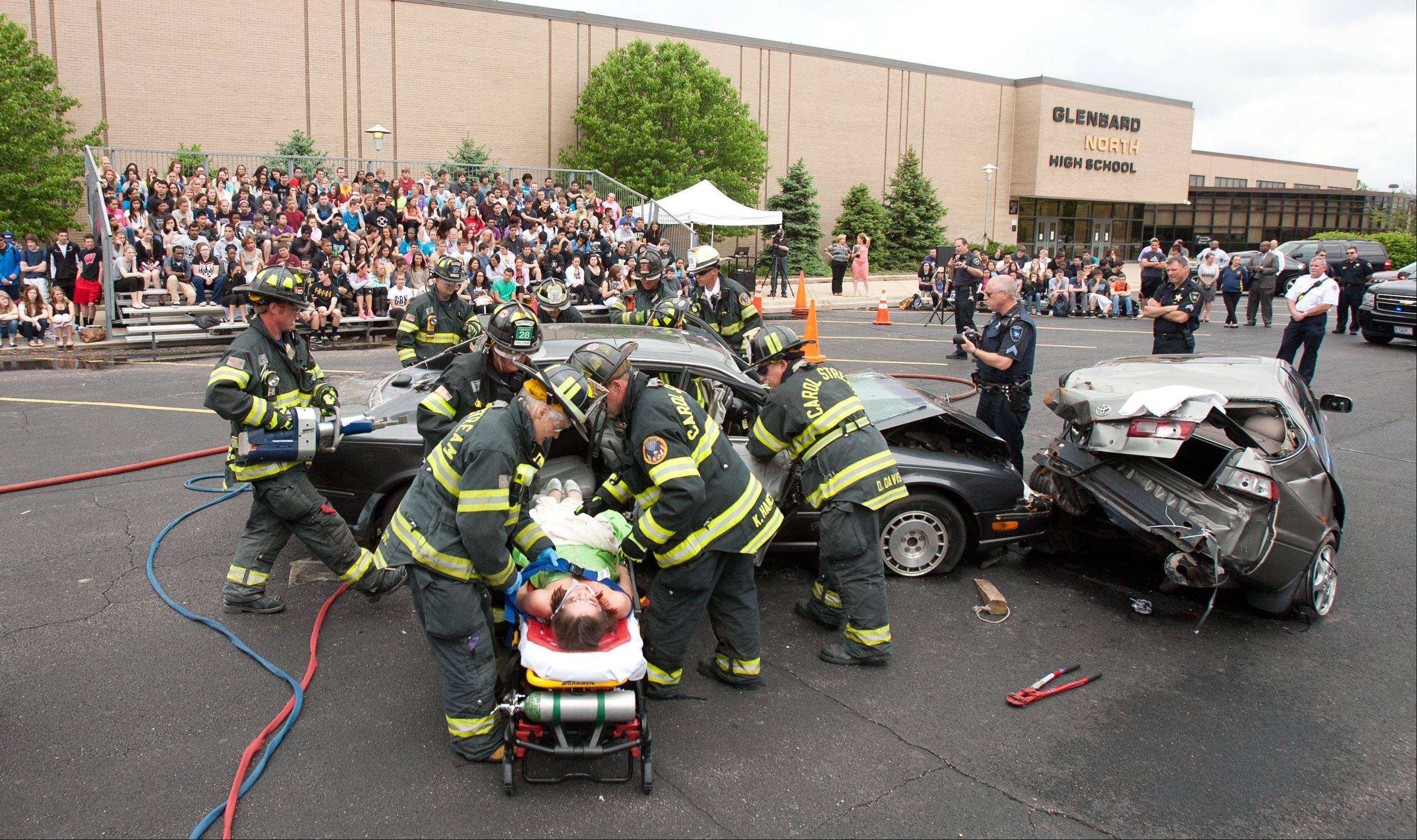 A student-actor playing a victim in a mock DUI crash is removed from a car Wednesday as part of the annual Operation Safe Celebration staged by the Carol Stream police and fire departments at Glenbard North High School.