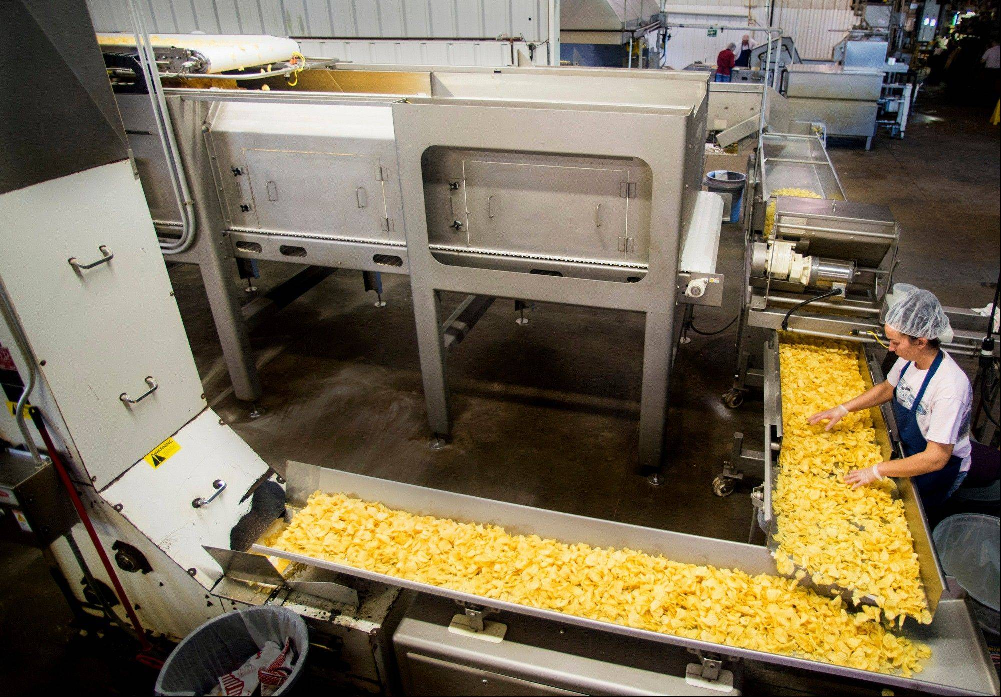 Production worker Sarah Gibson checks for quality as freshly cooked potato chips are gathered in an accumulator for packaging at Kitchen Cooked in Farmington.