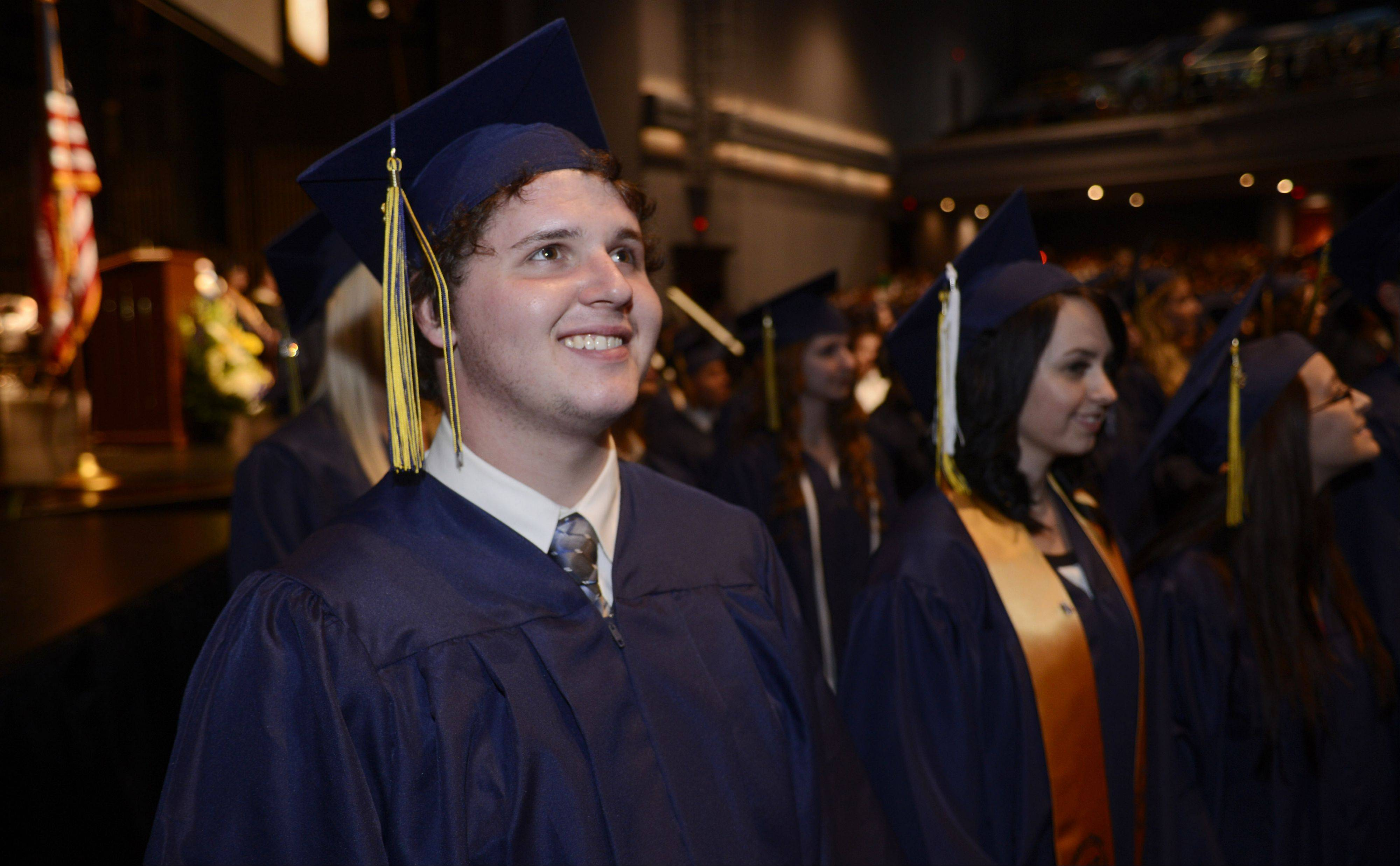 Anthony Brosman, left, and fellow classmates turn toward the audience during the processional of the East Leyden High School graduation at the Rosemont Theatre Tuesday.